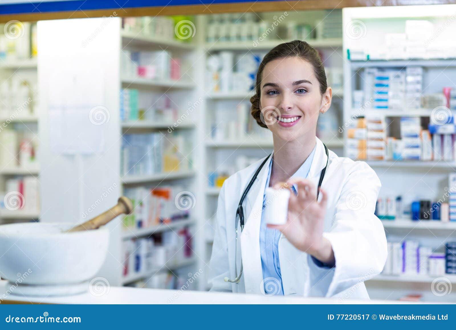 Χαμογελώντας φαρμακοποιός που παρουσιάζει εμπορευματοκιβώτιο ιατρικής στο φαρμακείο