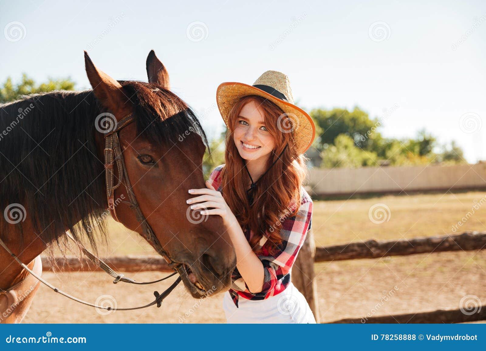 Χαμογελώντας όμορφη νέα γυναίκα cowgirl με το άλογό της στο αγρόκτημα