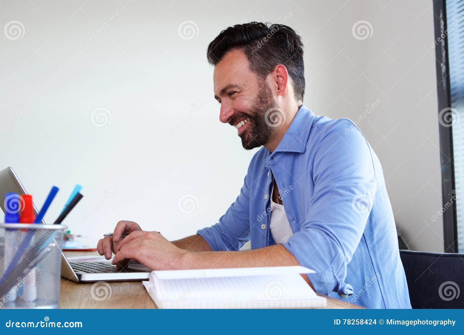 Χαμογελώντας ώριμο επιχειρησιακό άτομο που εργάζεται στο γραφείο του