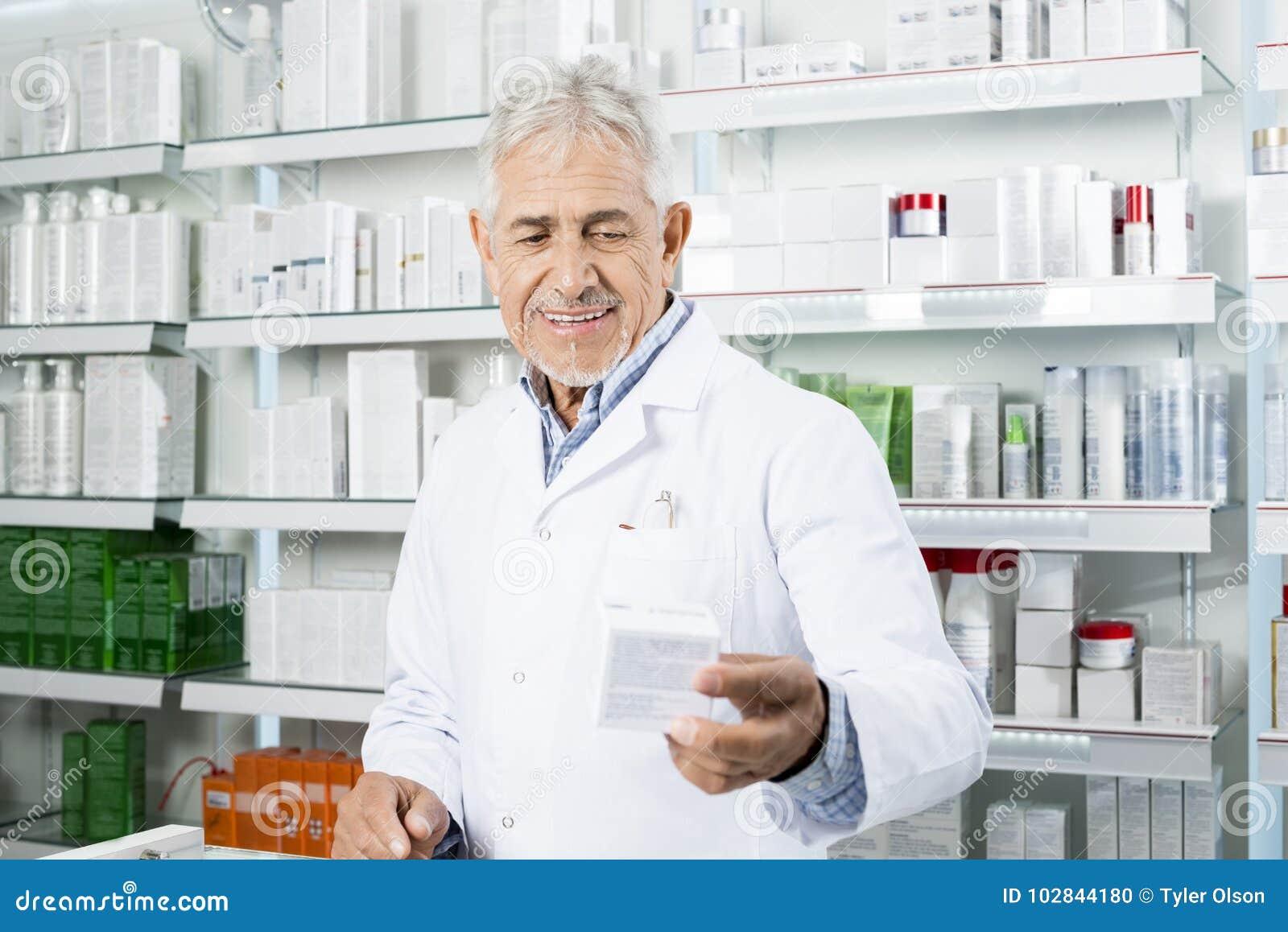 Χαμόγελο της ιατρικής εκμετάλλευσης φαρμακοποιών στο μετρητή στο φαρμακείο