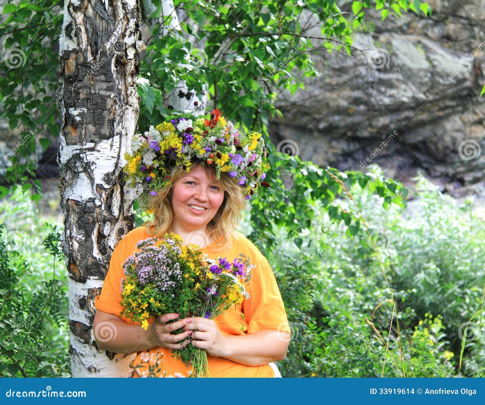 Χαμόγελο της όμορφης γυναίκας σε ένα στεφάνι λουλουδιών