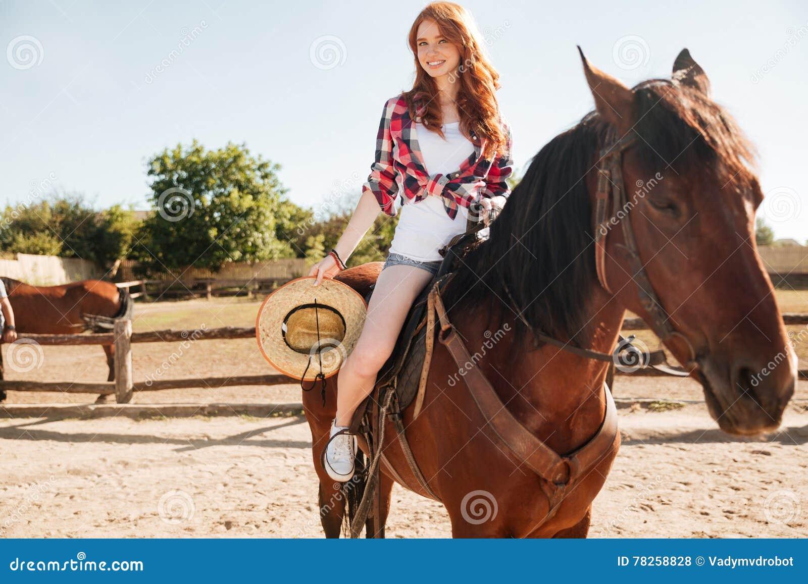 Χαμόγελο του αλόγου οδήγησης γυναικών cowgirl στο χωριό