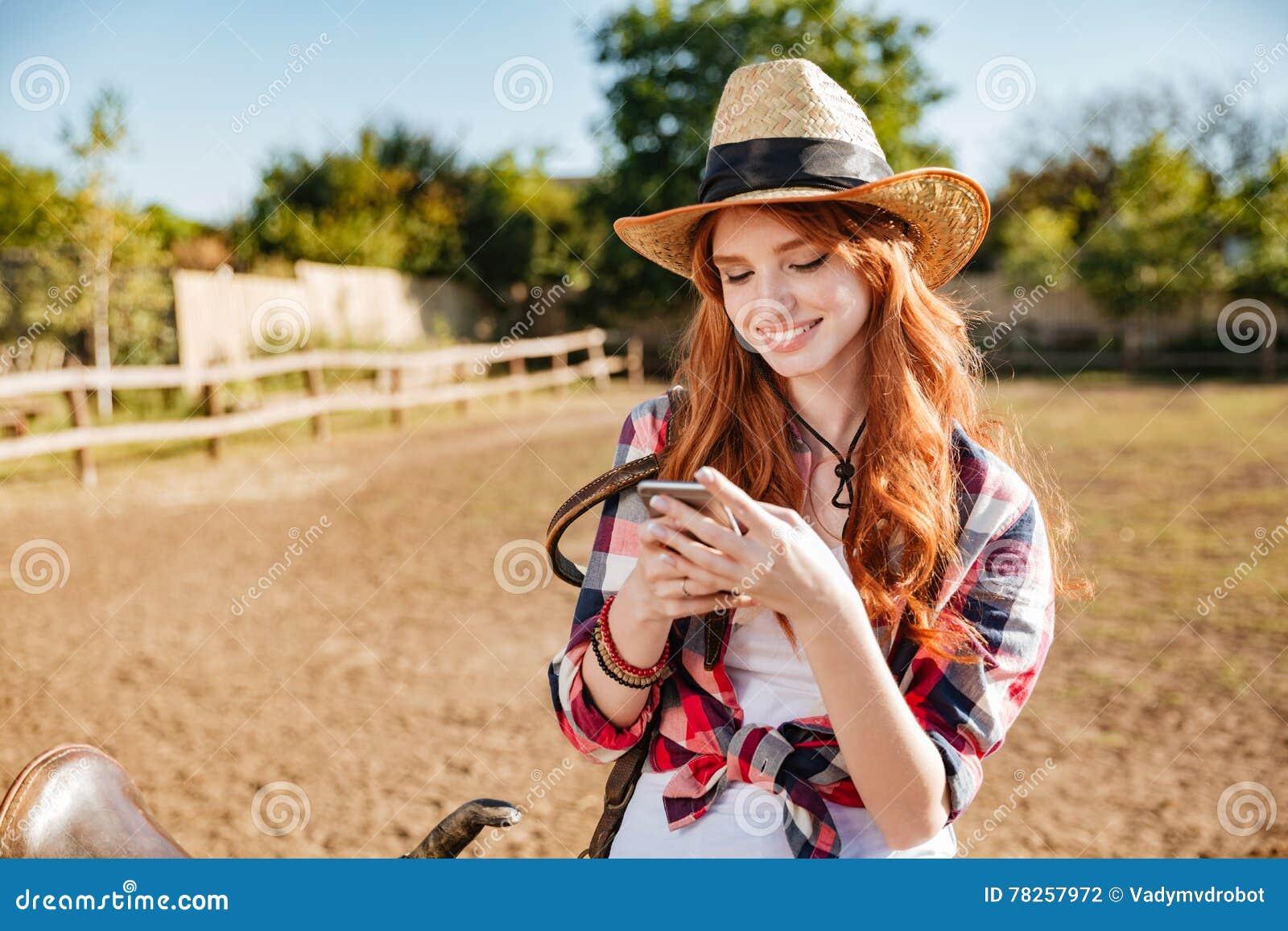 Χαμόγελο cowgirl χρησιμοποιώντας το κινητό τηλέφωνο στεμένος στο φράκτη αγροκτημάτων
