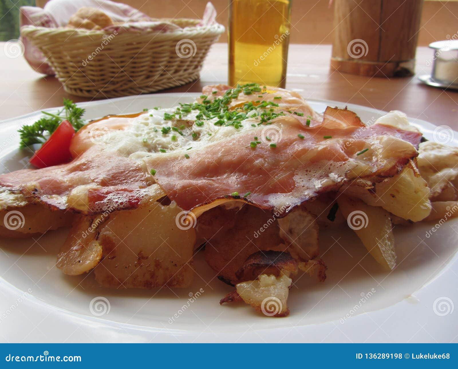 Χαρακτηριστικό νότιο τυρολέζικο πιάτο με speck, τα τηγανισμένα αυγά, τις πατάτες και το φρέσκο κρεμμύδι