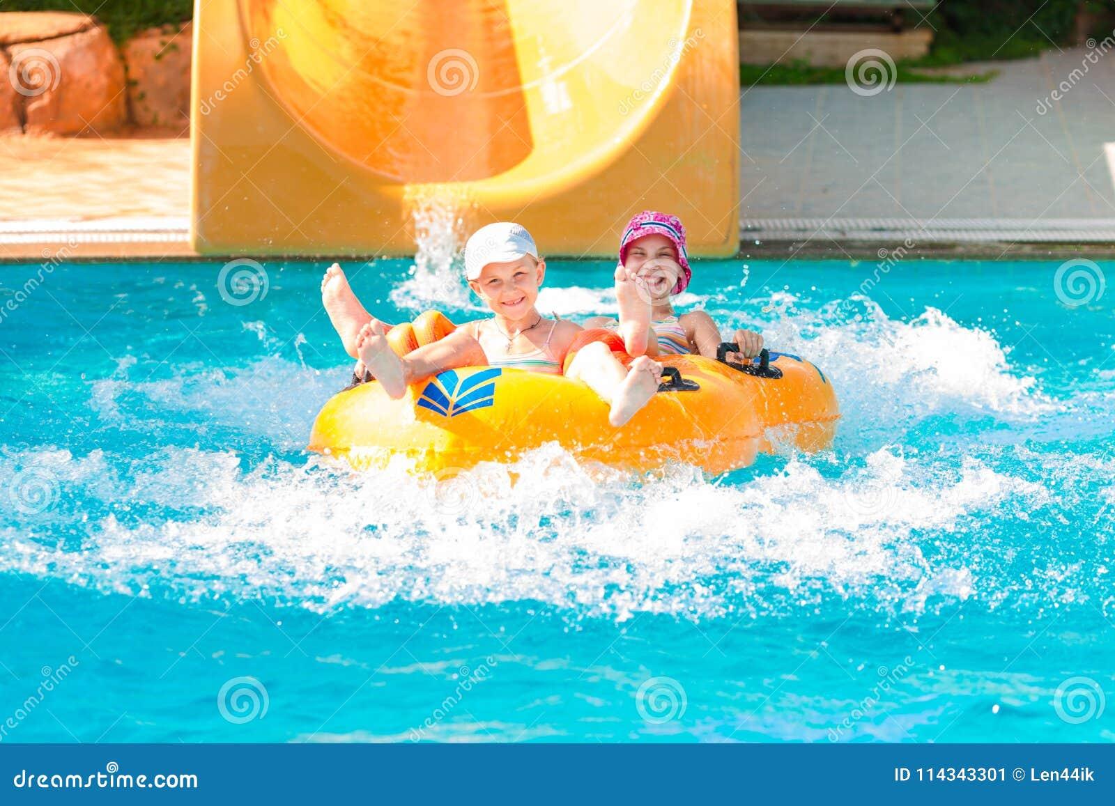 Χαριτωμένα ευτυχή κορίτσια στο amusment aquapark
