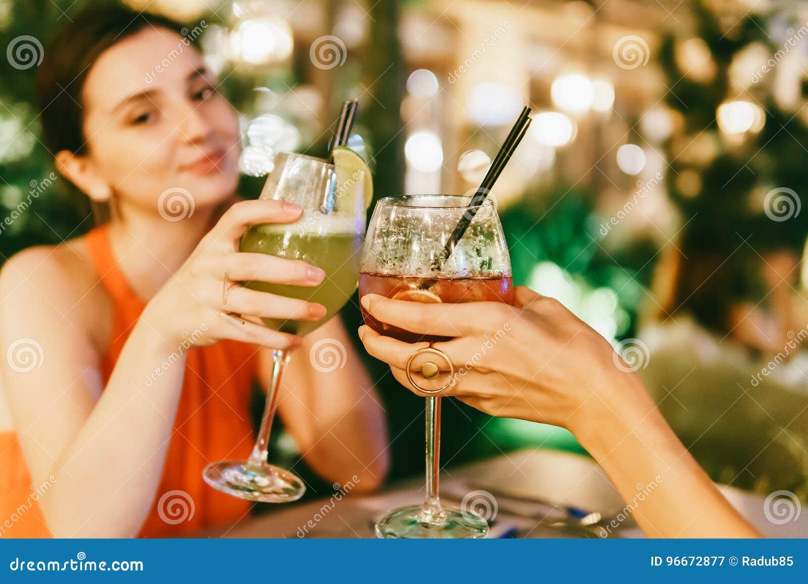 Χαριτωμένα κορίτσια που γιορτάζουν τη νύχτα έξω με τα ποτά κοκτέιλ