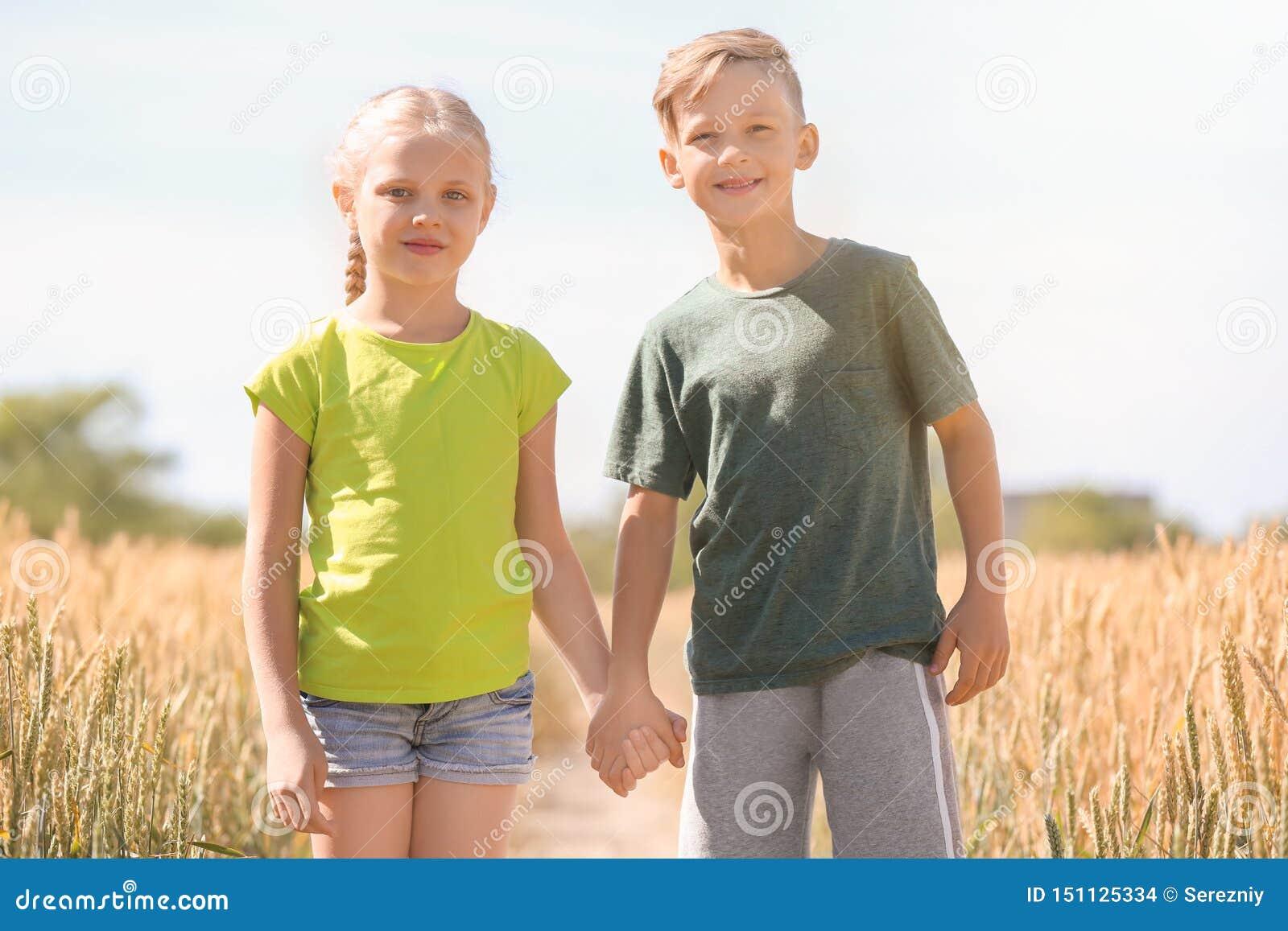 Χαριτωμένα μικρά παιδιά στον τομέα σίτου την ηλιόλουστη ημέρα
