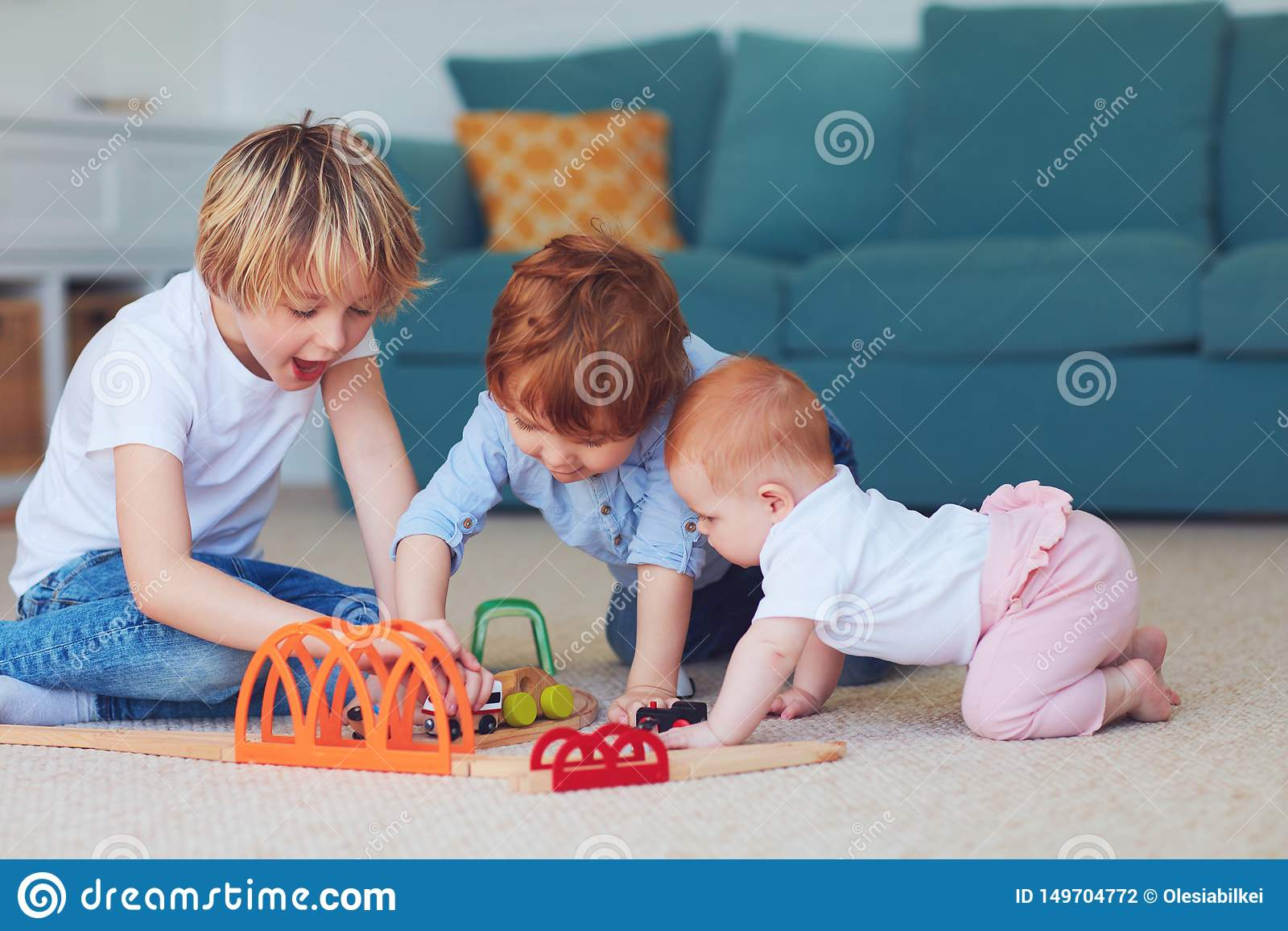Χαριτωμένα παιδιά, αμφιθαλείς που παίζουν τα παιχνίδια μαζί στον τάπητα στο σπίτι
