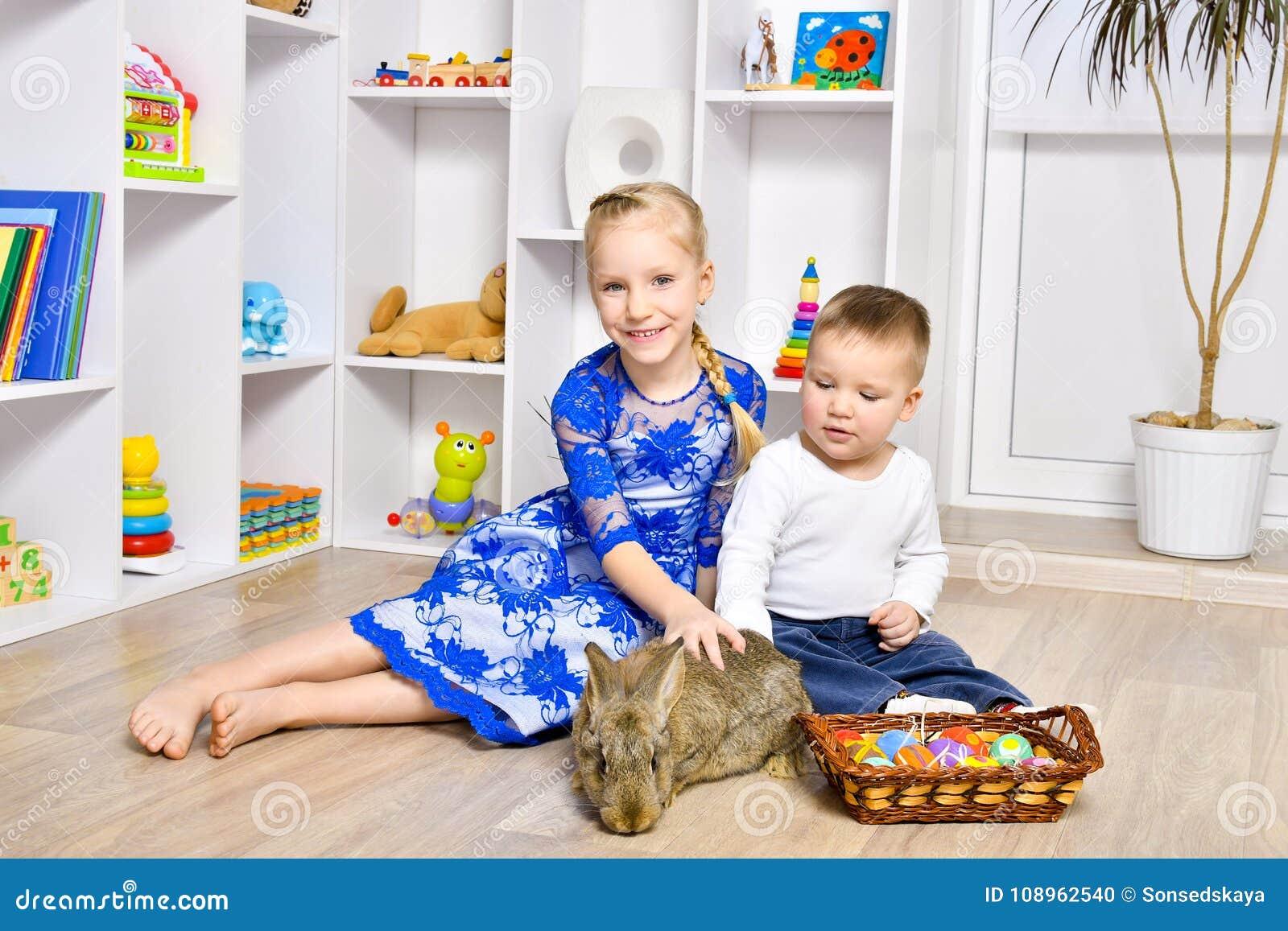 Χαριτωμένα παιδιά που παίζουν με ένα κουνέλι για Πάσχα