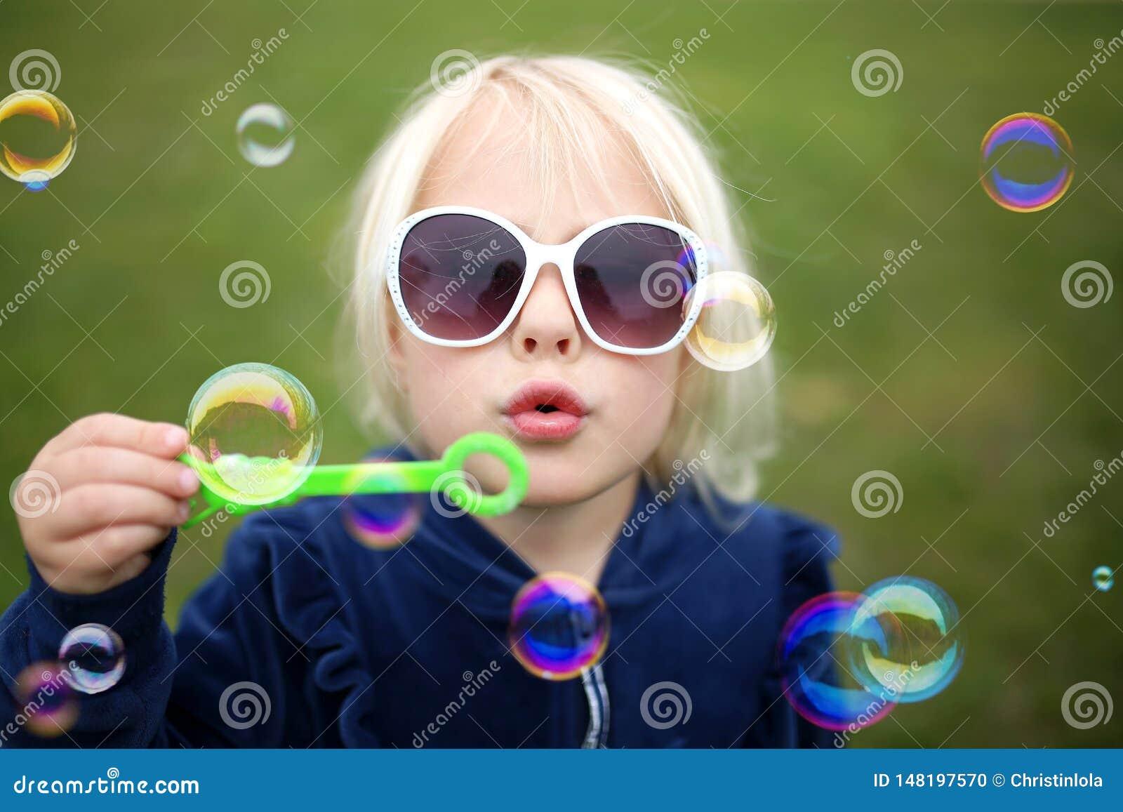 Χαριτωμένες φυσώντας φυσαλίδες παιδιών μικρών κοριτσιών έξω μια θερινή ημέρα