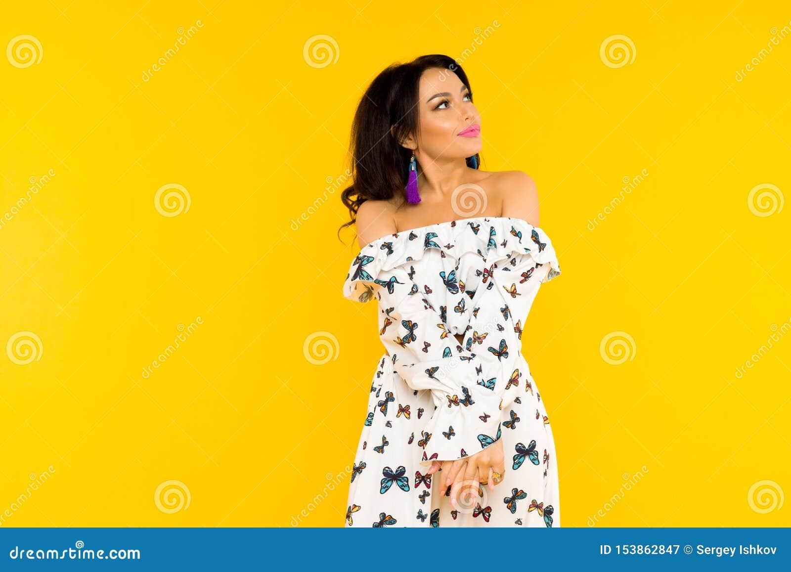 Χαριτωμένη ασιατική γυναίκα στο φόρεμα μεταξιού με τις πεταλούδες που θέτει στο κίτρινο υπόβαθρο