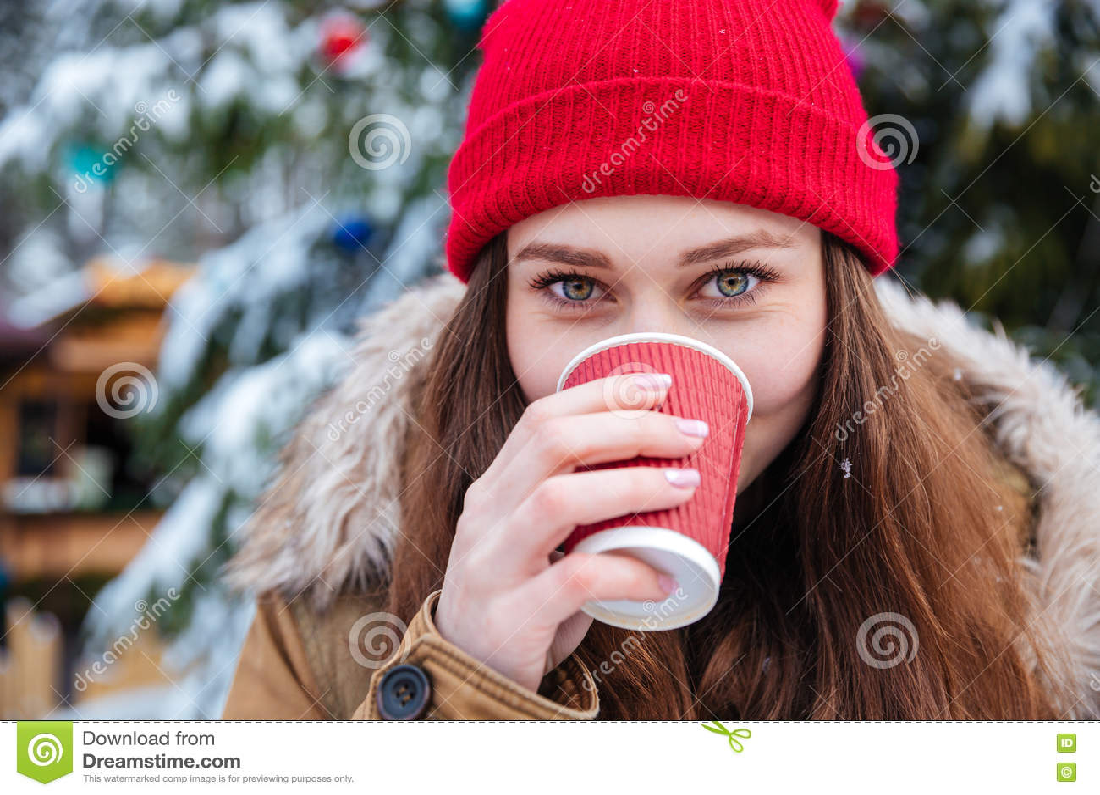 Χαριτωμένη γυναίκα που πίνει τον καυτό καφέ υπαίθρια το χειμώνα