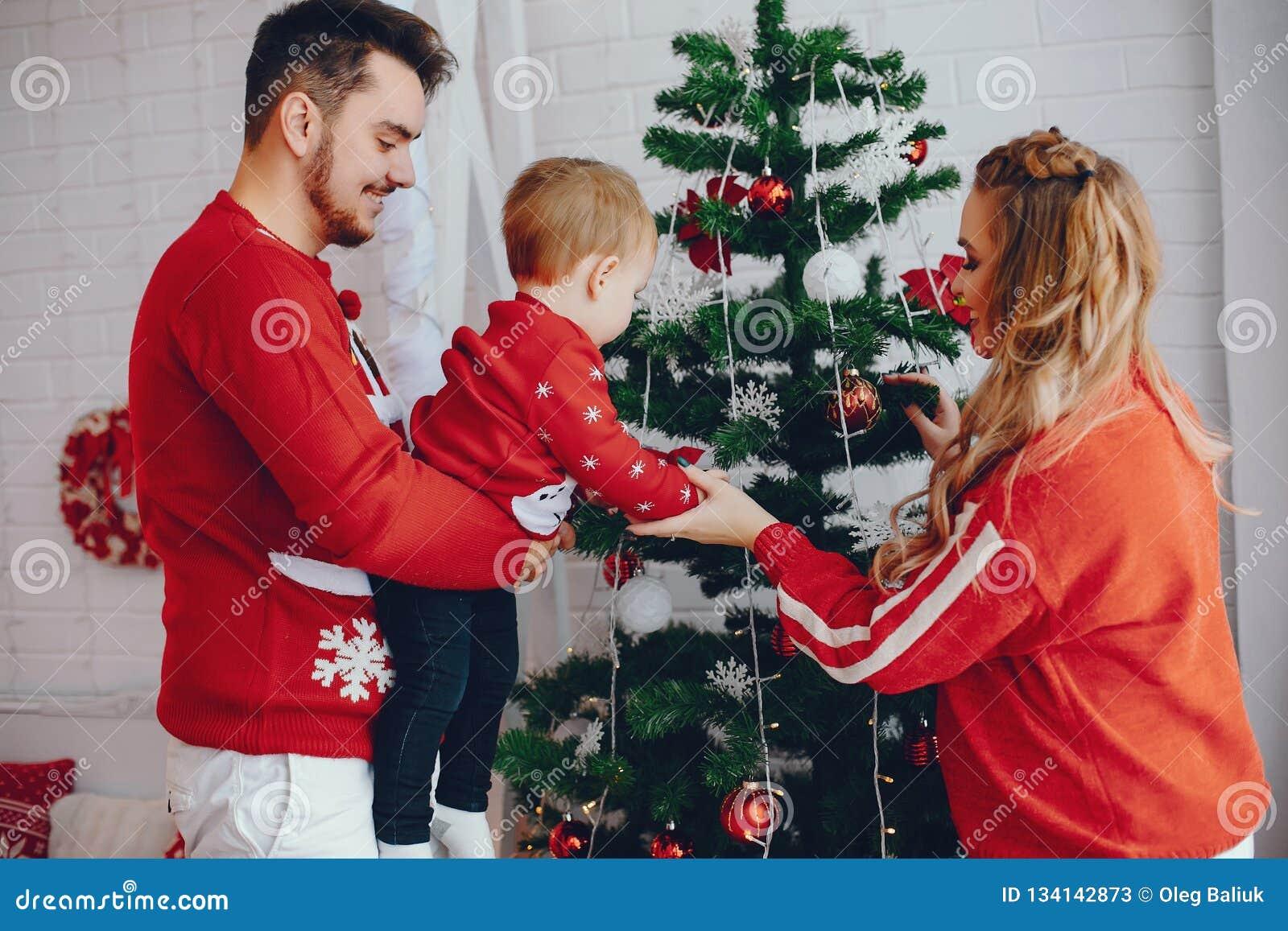 Χαριτωμένη νέα οικογένεια που στέκεται κοντά στο χριστουγεννιάτικο δέντρο