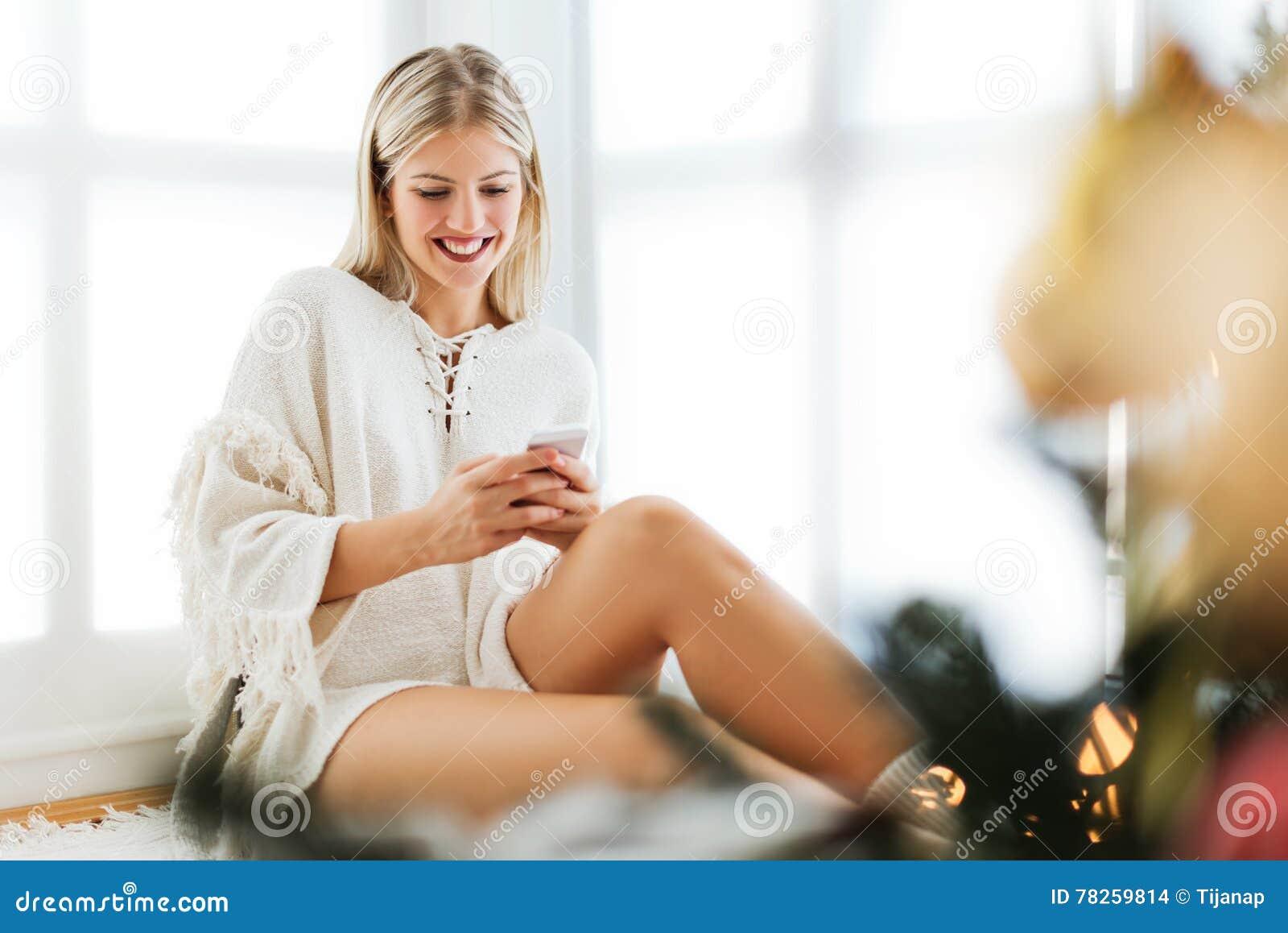 Χαριτωμένη, νέα συνεδρίαση γυναικών δίπλα σε ένα χριστουγεννιάτικο δέντρο, που χρησιμοποιεί ένα τηλέφωνο κυττάρων