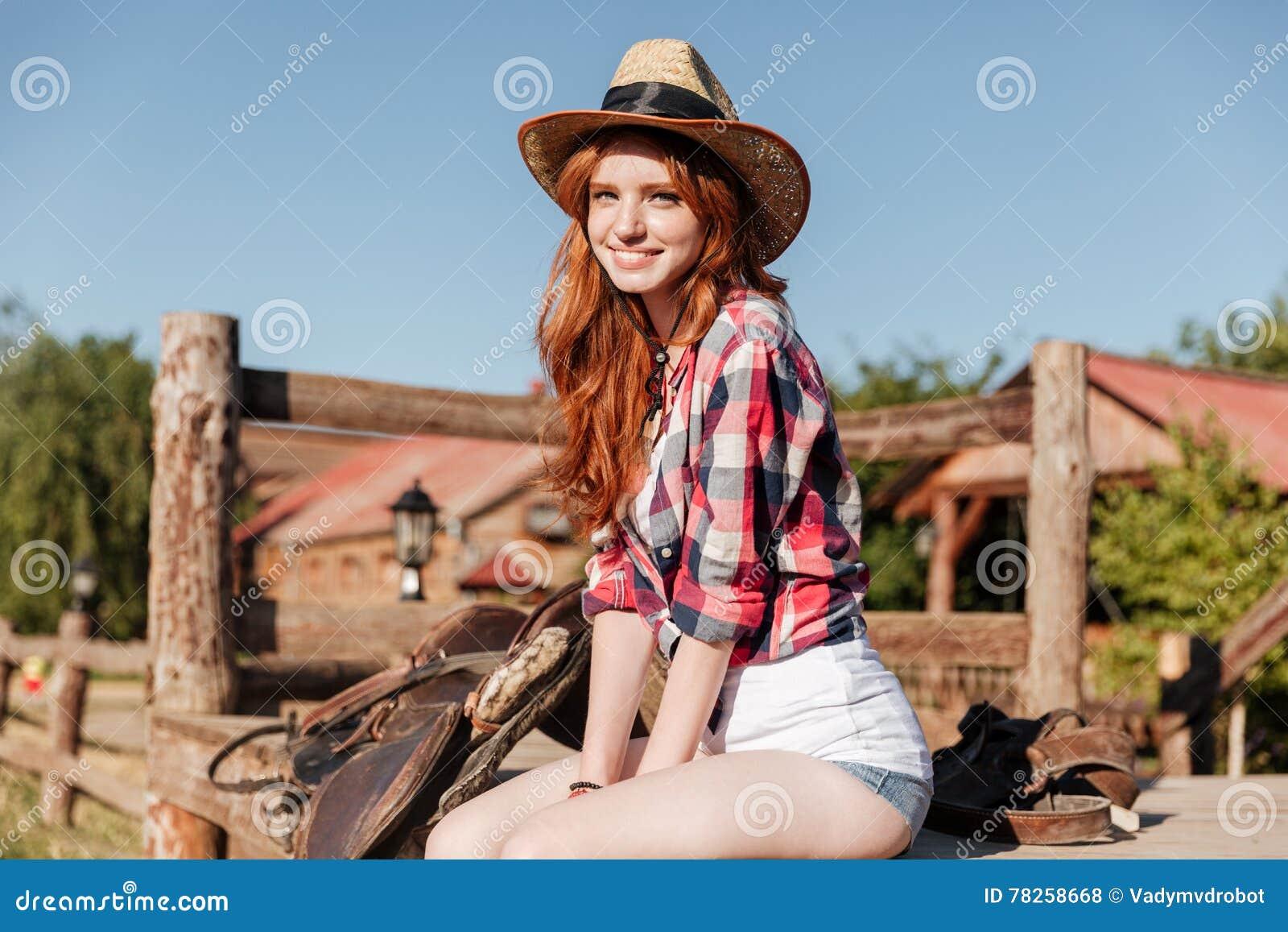 Χαριτωμένη redhead συνεδρίαση cowgirl και στήριξη στο φράκτη αγροκτημάτων
