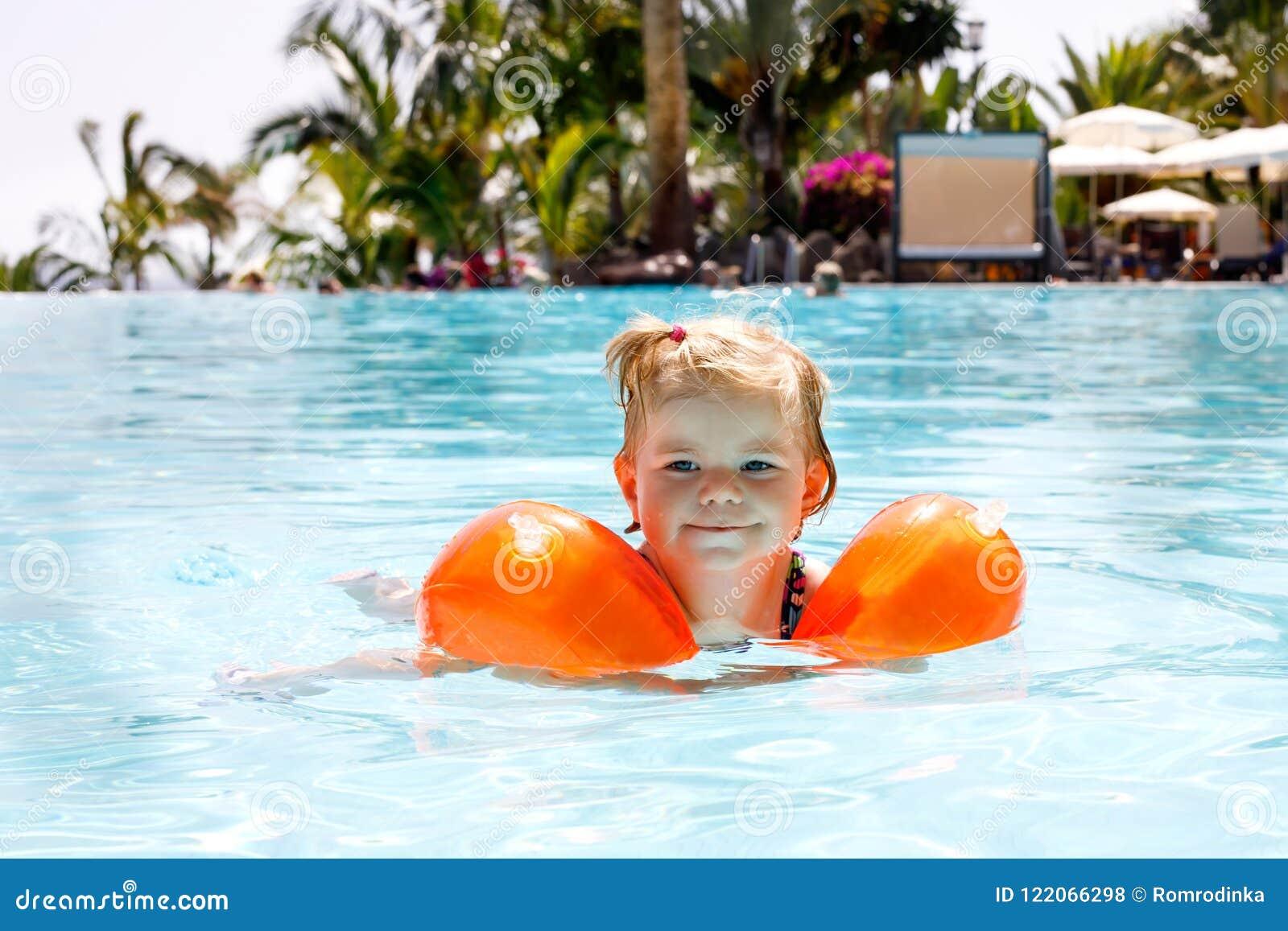 Χαριτωμένος ευτυχής λίγο κορίτσι μικρών παιδιών που κολυμπά στη λίμνη και που έχει τη διασκέδαση στις οικογενειακές διακοπές σε έ