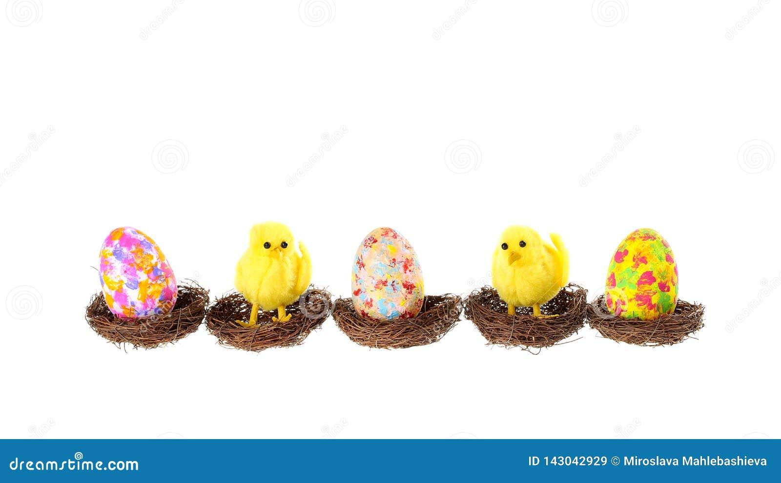 Χαριτωμένο έμβλημα Πάσχας με τρία ζωηρόχρωμα χρωματισμένα αυγά και δύο διακοσμητικά κοτόπουλα που κάθονται στις φωλιές πουλιών, π
