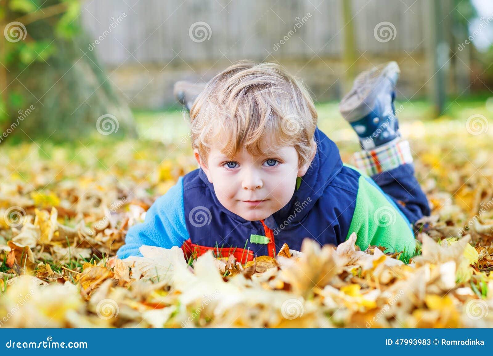 Χαριτωμένο αγόρι παιδιών που έχει τη διασκέδαση στο πάρκο φθινοπώρου