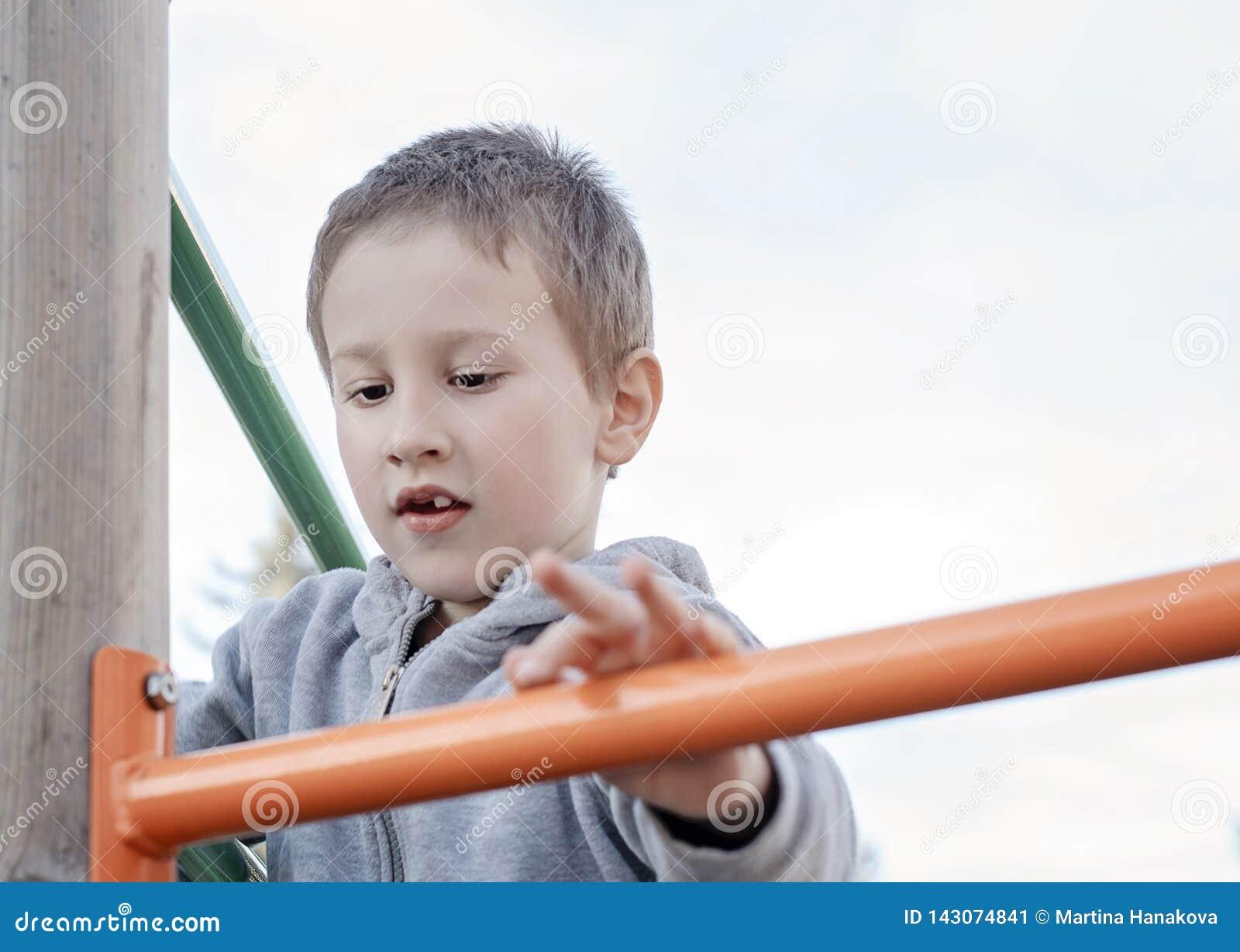 Χαριτωμένο αγόρι που αναρριχείται στην παιδική χαρά παιδιών υπαίθρια Προσχολικό παιδί που έχει τη διασκέδαση στην παιδική χαρά Πα