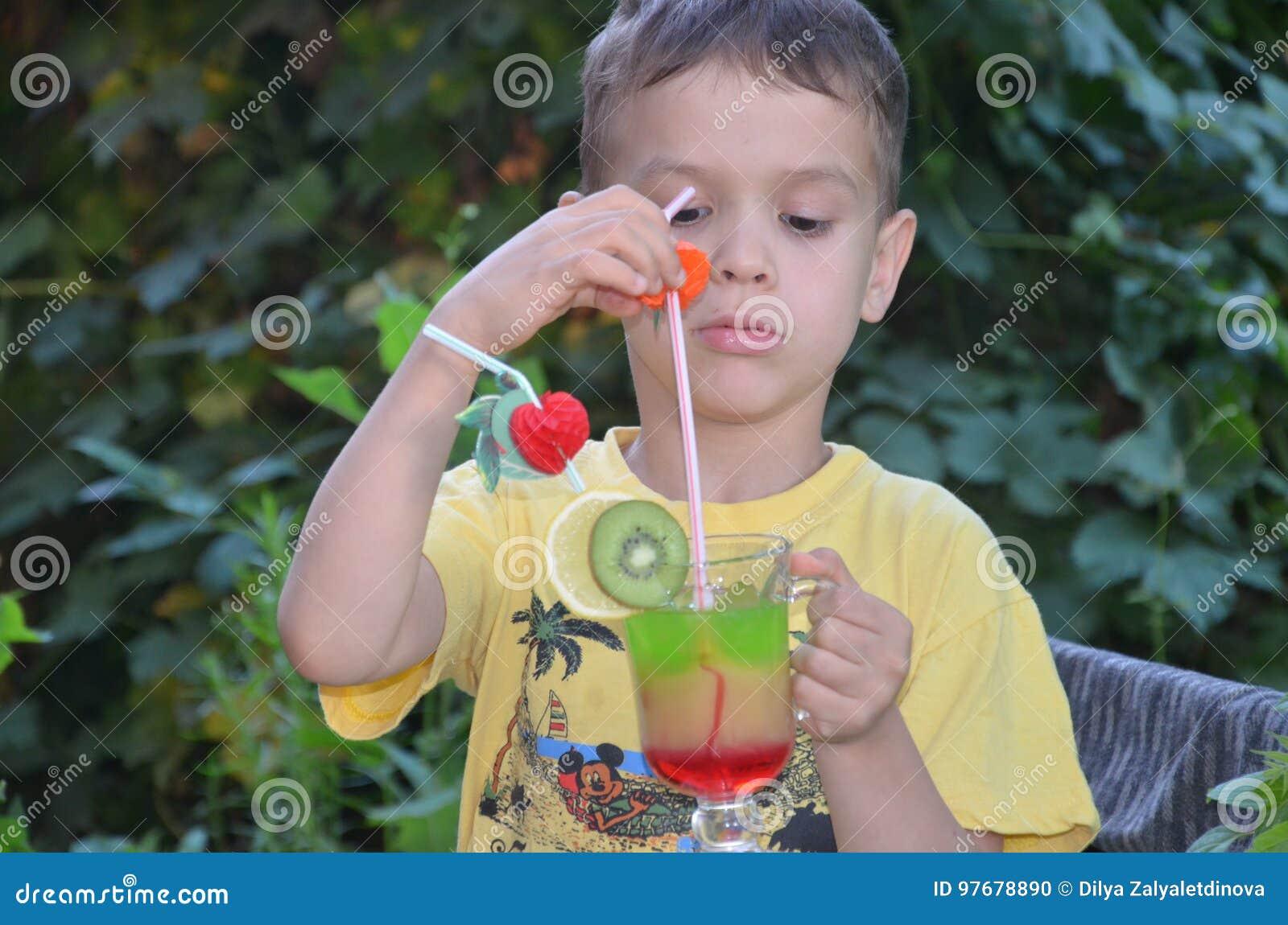 Χαριτωμένο αγόρι που πίνει τον υγιή καταφερτζή χυμού φρούτων κοκτέιλ το καλοκαίρι Ευτυχές παιδί που απολαμβάνει το οργανικό ποτό