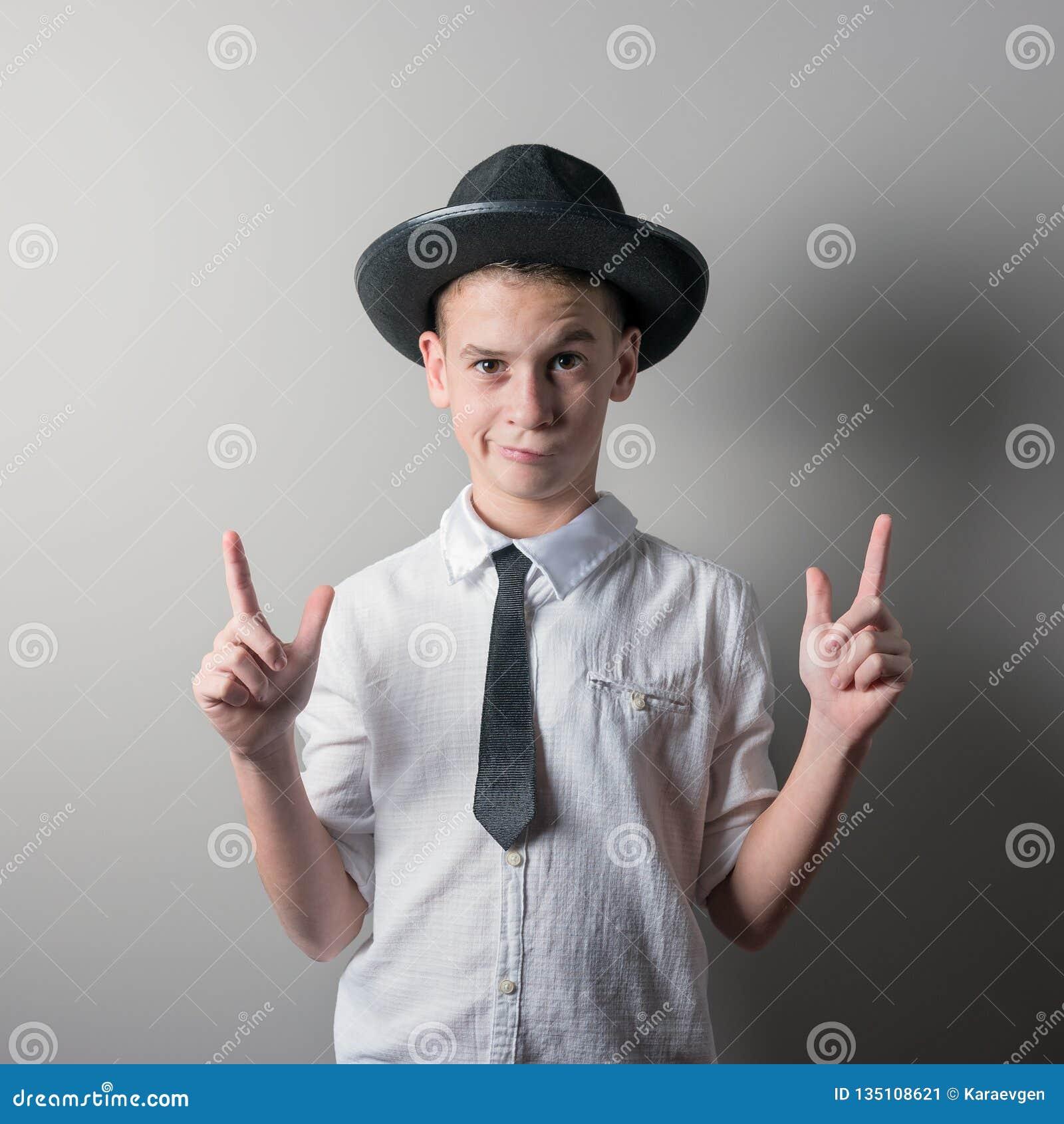 Χαριτωμένο αγόρι στο μαύρο καπέλο και λευκό πουκάμισο στο φωτεινό υπόβαθρο