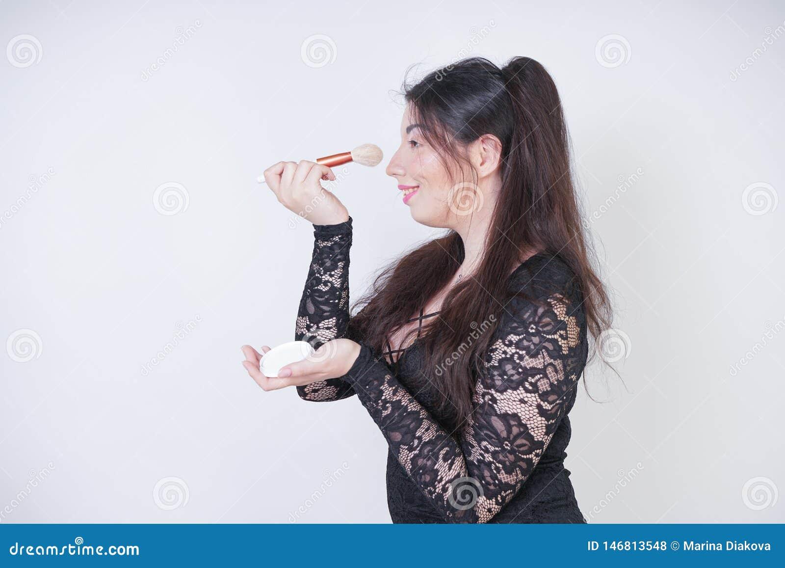 Χαριτωμένο ασιατικό κορίτσι στο μαύρο φόρεμα βραδιού δαντελλών με τη σκόνη και μια βούρτσα στα χέρια στο άσπρο υπόβαθρο