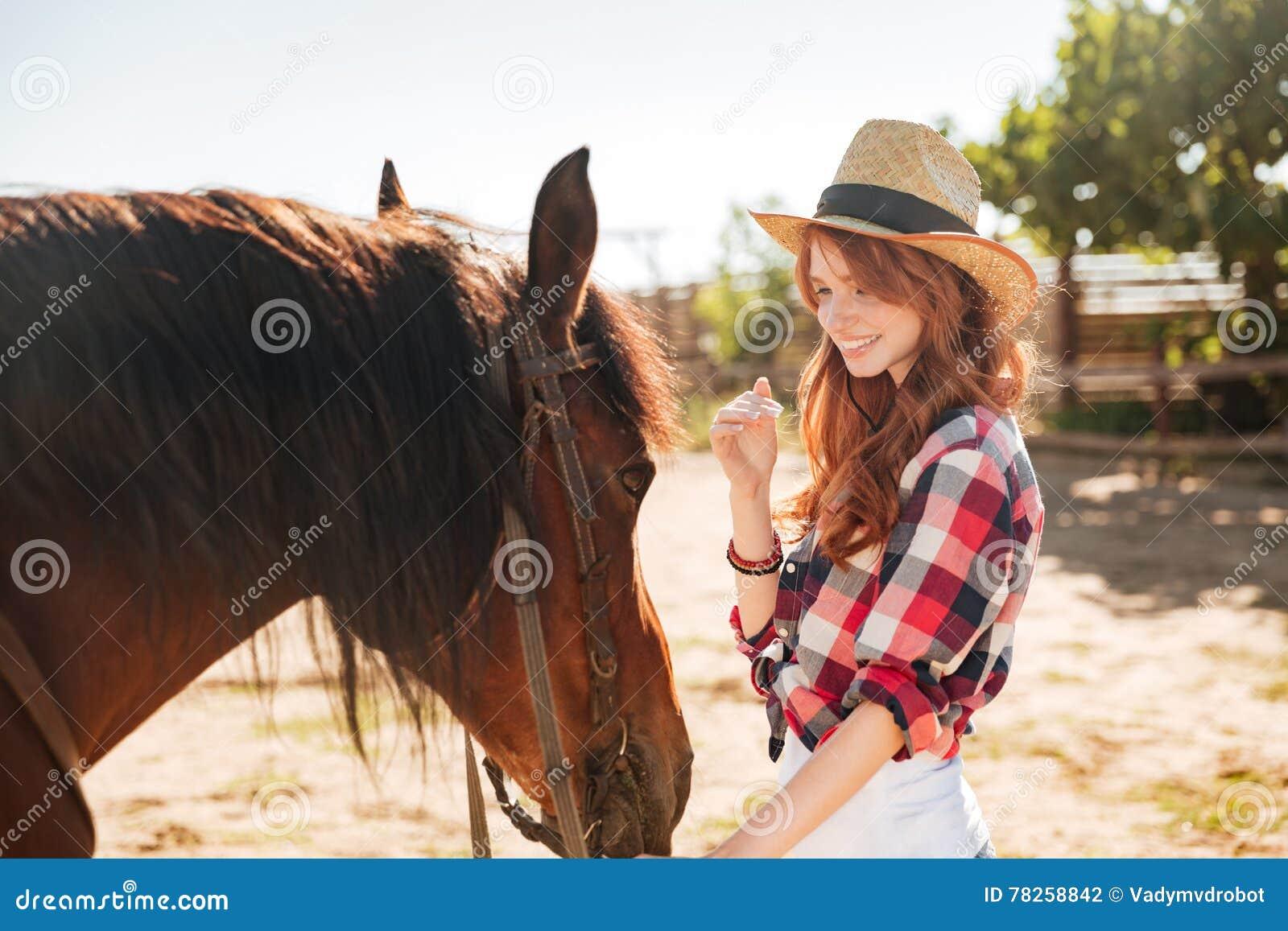 Χαριτωμένο καλό cowgirl που φροντίζει το άλογό της στο αγρόκτημα