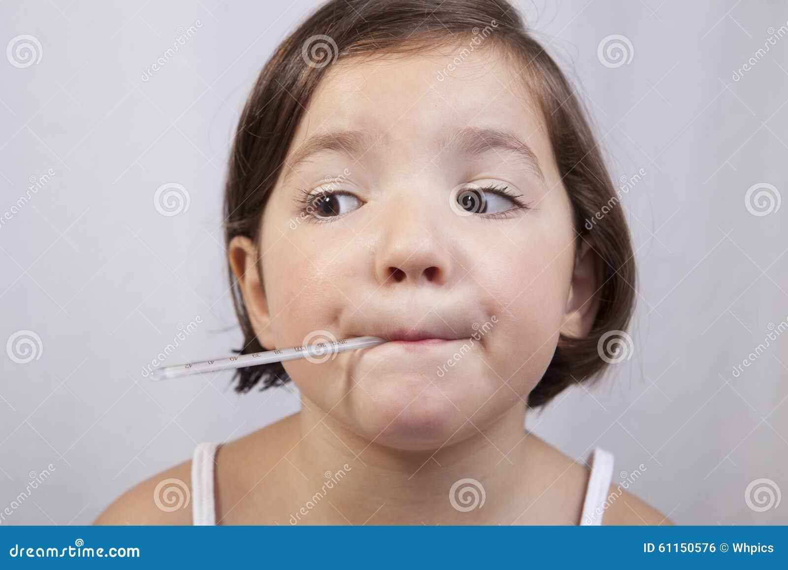 Χαριτωμένο κορίτσι με ένα κλινικό θερμόμετρο υδράργυρος--γυαλιού
