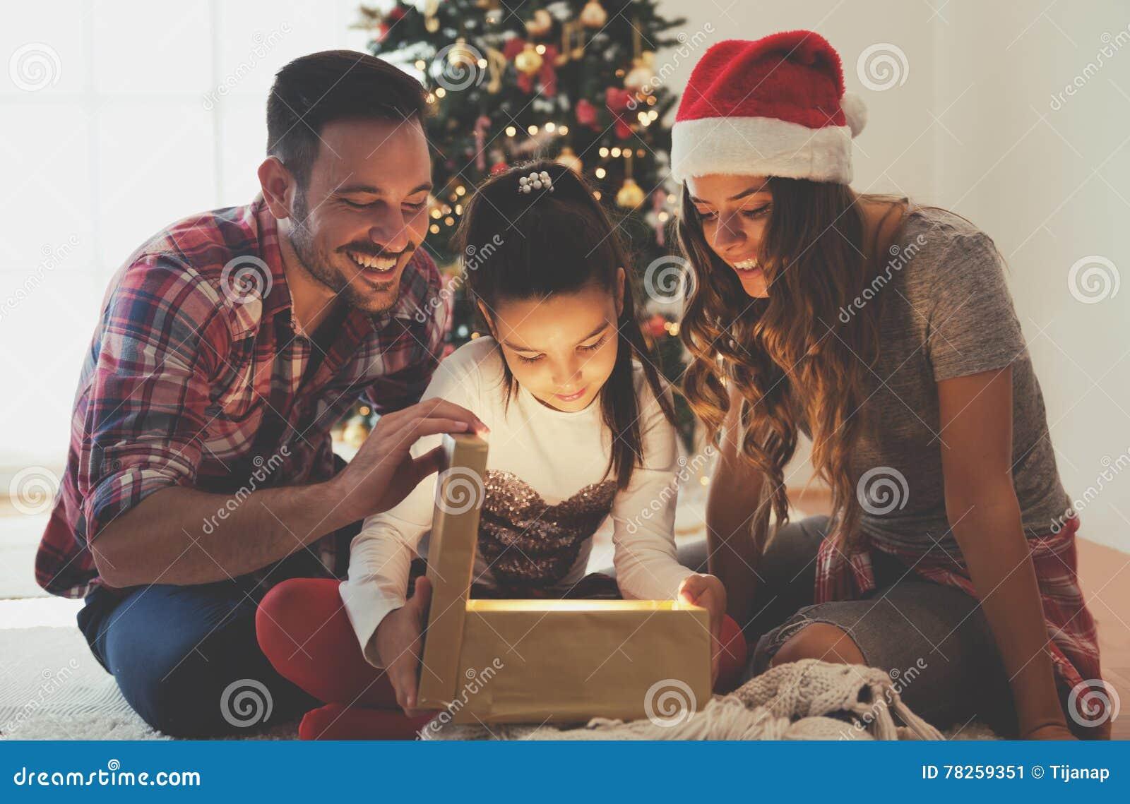 Χαριτωμένο κορίτσι που ανοίγει ένα παρόν σε ένα πρωί Χριστουγέννων με την οικογένειά της