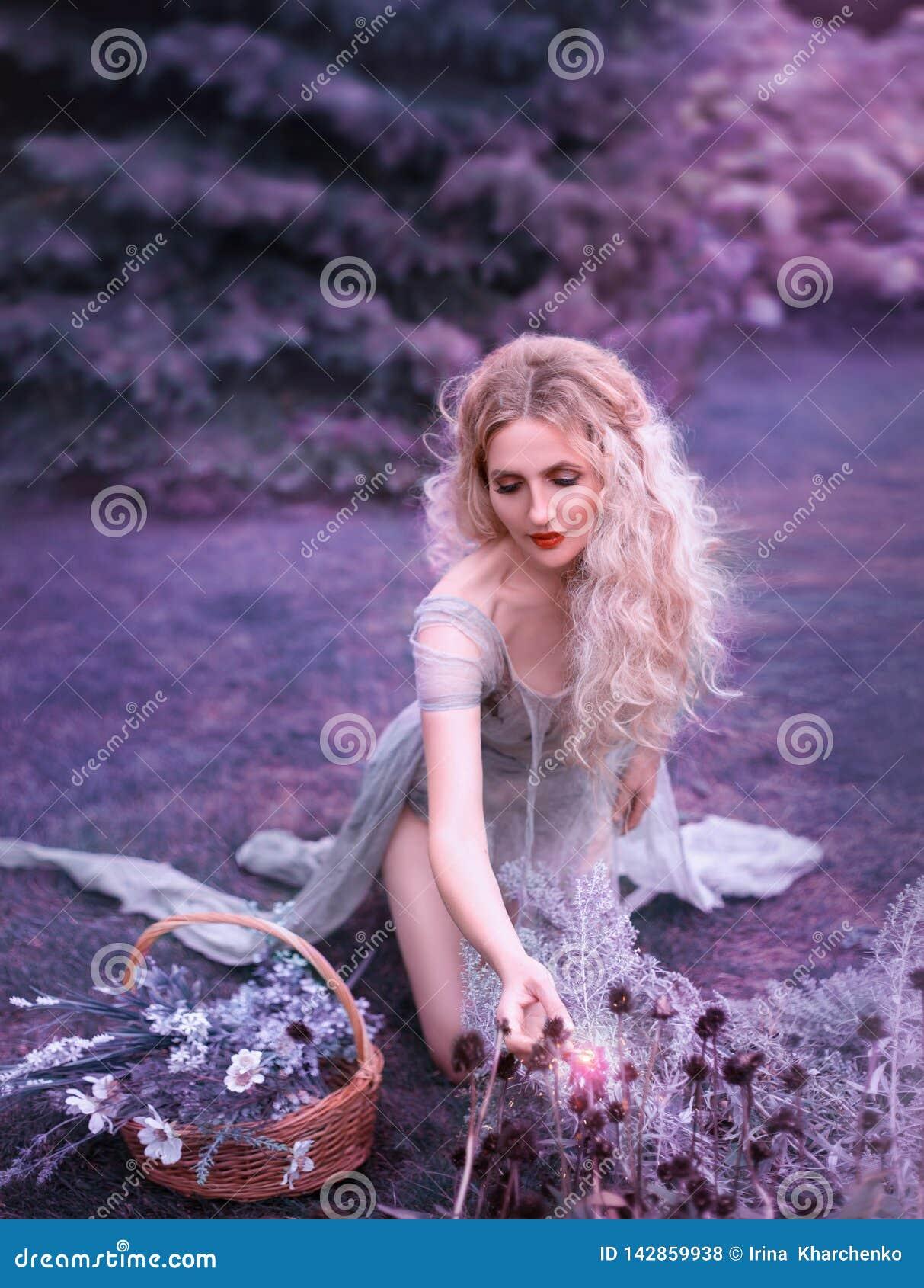 Χαριτωμένο κορίτσι στο παλαιό γκρίζο φόρεμα με το πολύ κομμένο τραίνο και τα ανοικτά πόδια που κάθονται στα γόνατα και που συλλέγ