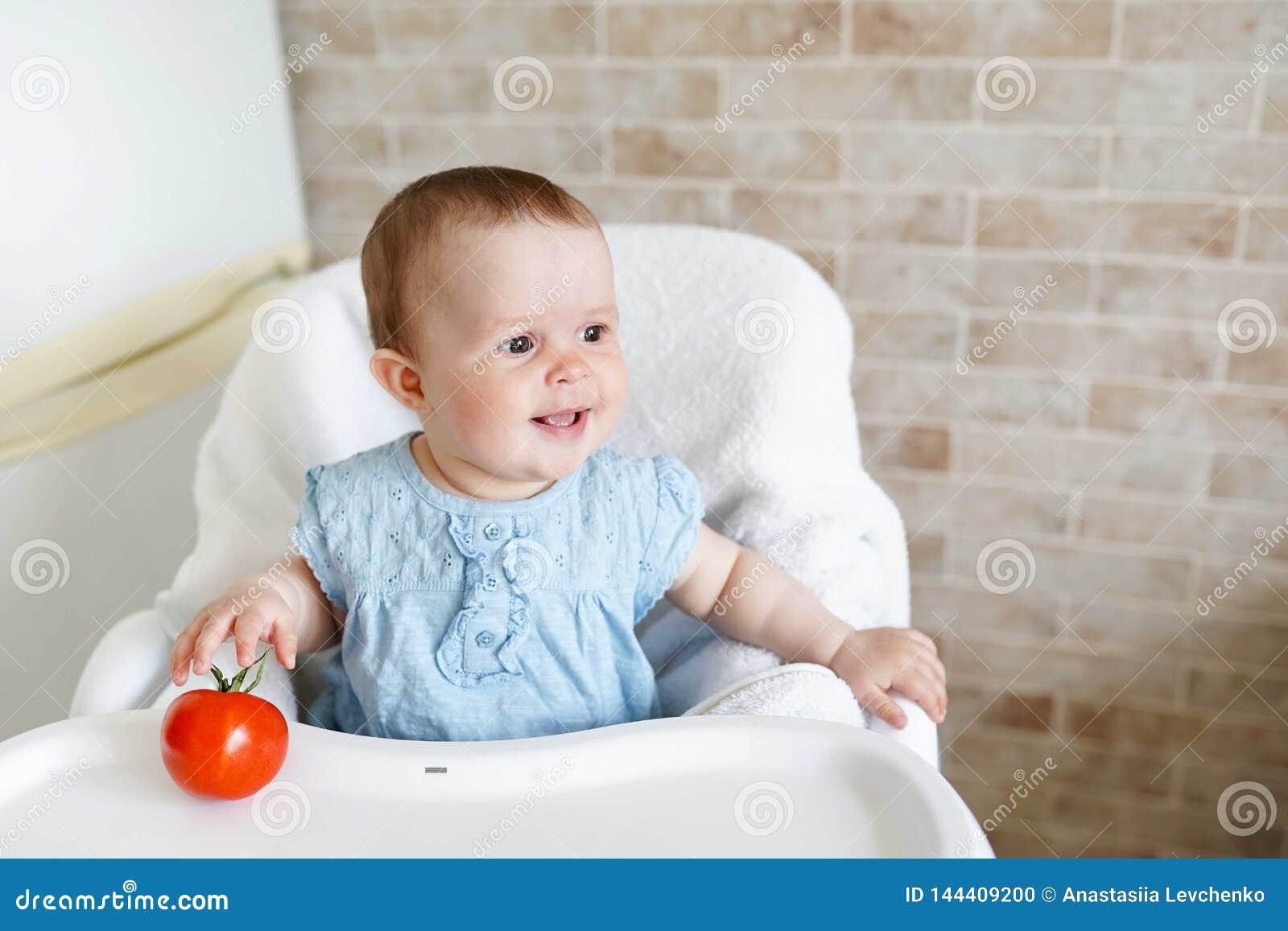 Χαριτωμένο μικρό κορίτσι παιδιών που τρώει τα υγιή τρόφιμα στον παιδικό σταθμό Μωρό στην καρέκλα