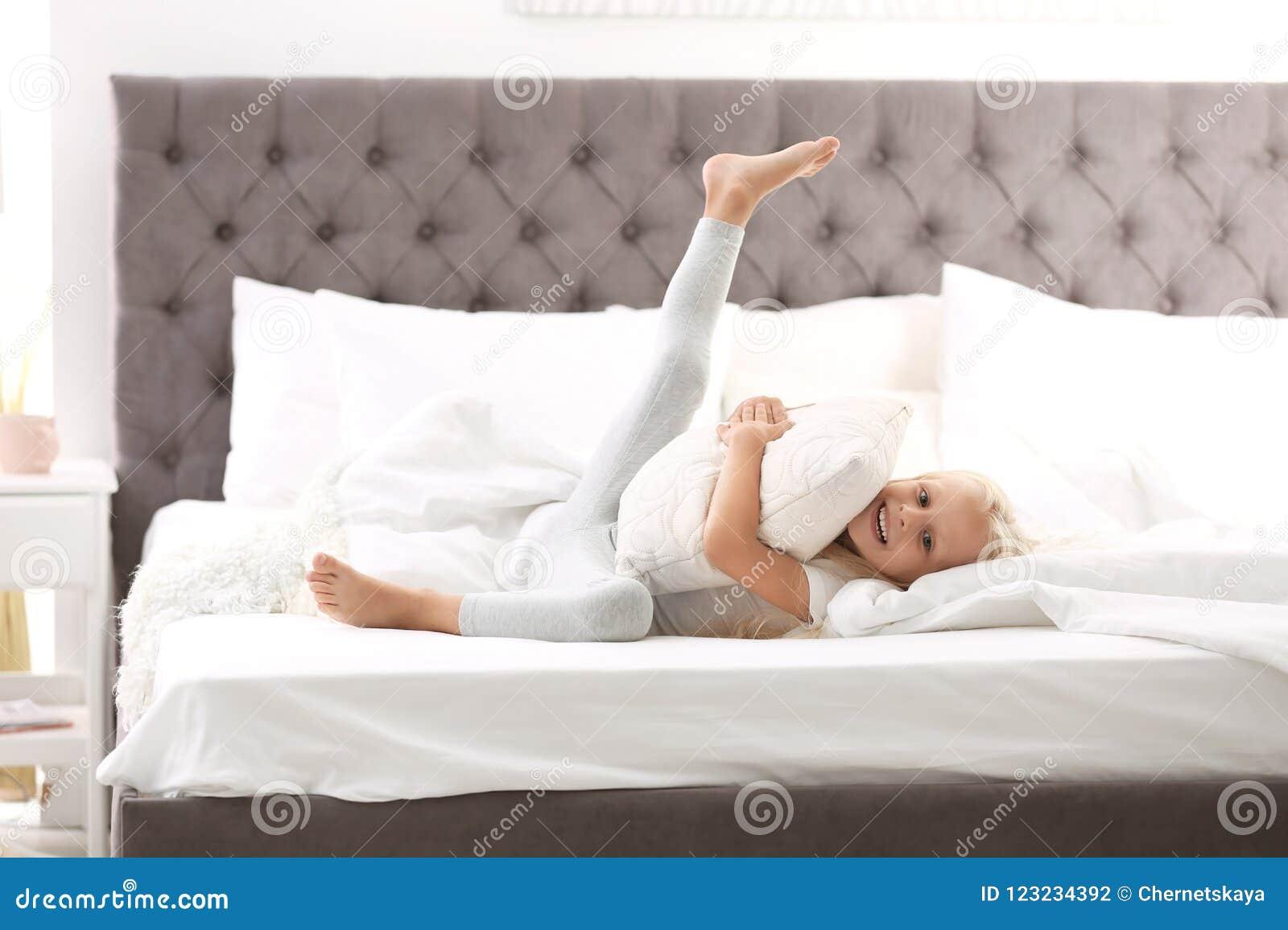 Χαριτωμένο μικρό κορίτσι που αγκαλιάζει το μαξιλάρι στο κρεβάτι