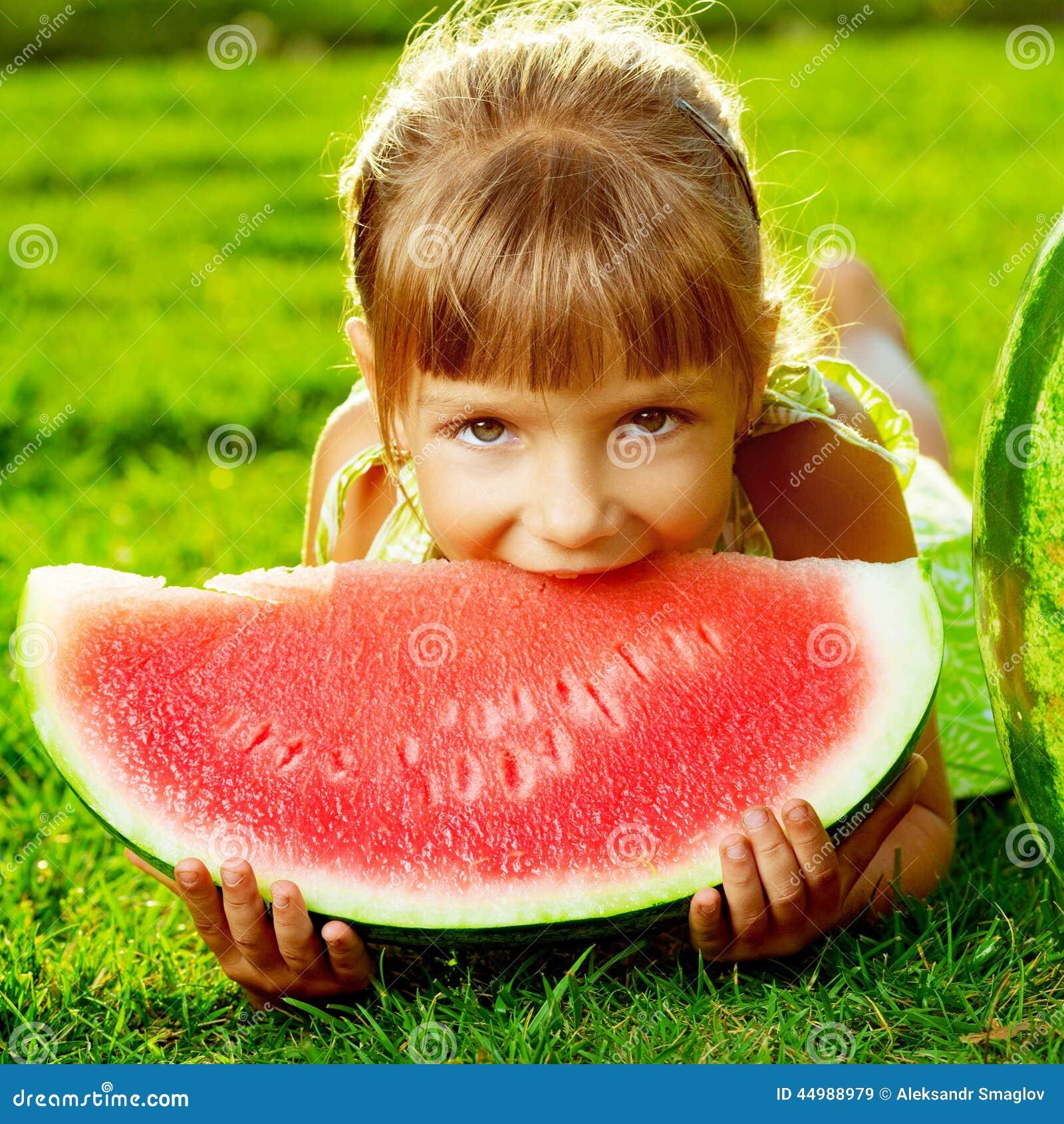 Χαριτωμένο μικρό κορίτσι που τρώει το καρπούζι και που βρίσκεται στην πράσινη χλόη