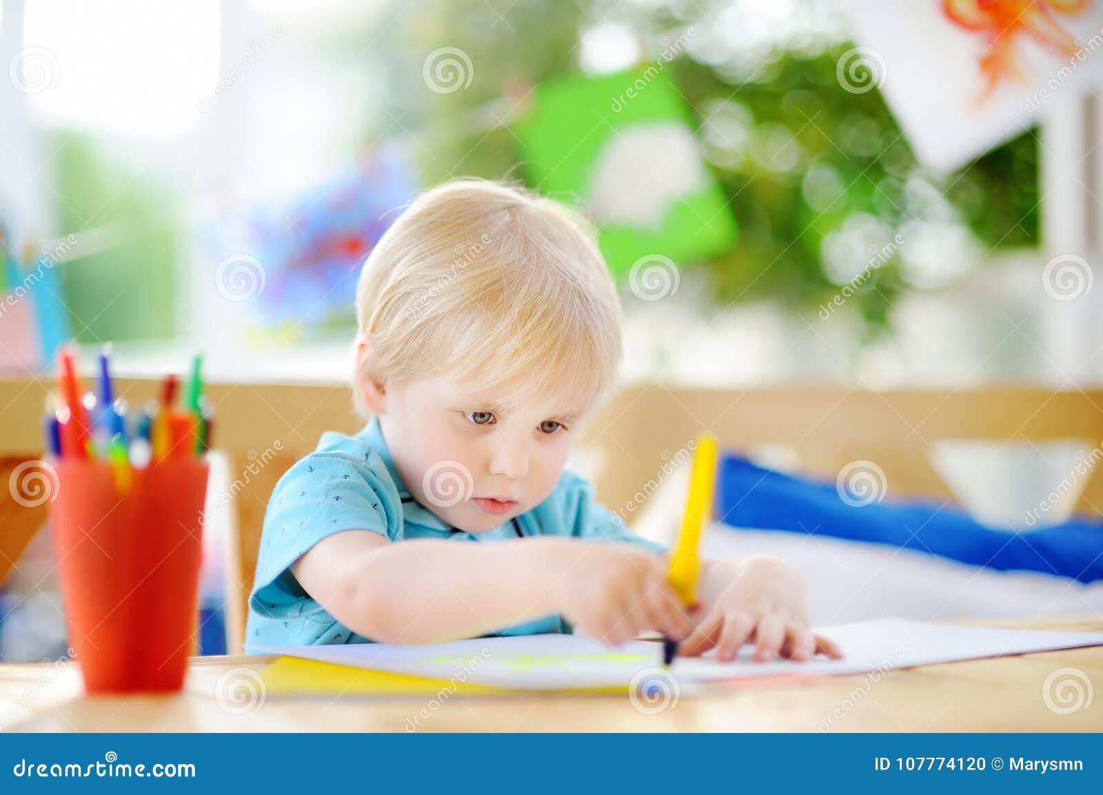 Χαριτωμένο μικρό παιδί που σύρει και που χρωματίζει με τις ζωηρόχρωμες μάνδρες δεικτών στον παιδικό σταθμό