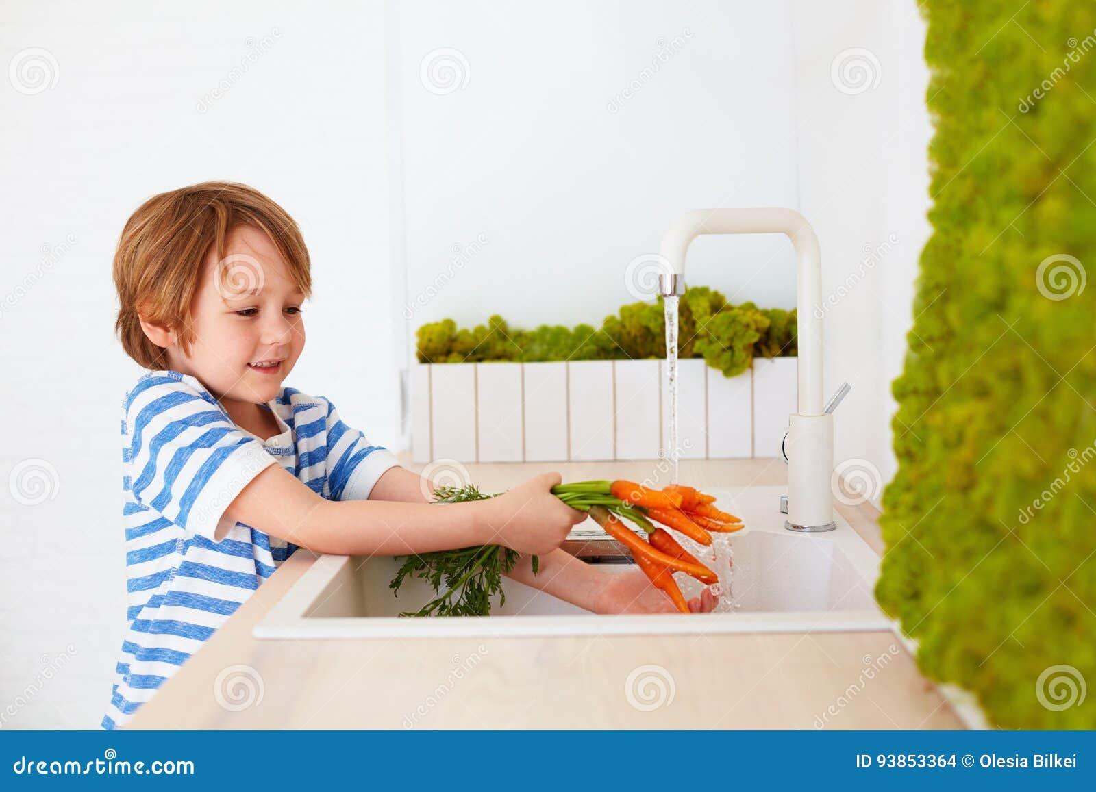 Χαριτωμένο νέο αγόρι που πλένει τα καρότα κάτω από το νερό βρύσης στην κουζίνα