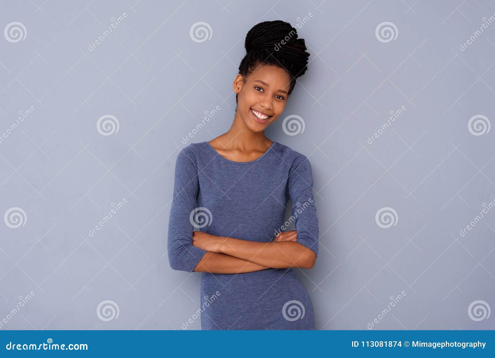 Χαριτωμένο νέο κορίτσι που στέκεται με τα όπλα που διασχίζονται και που χαμογελά στο γκρίζο κλίμα