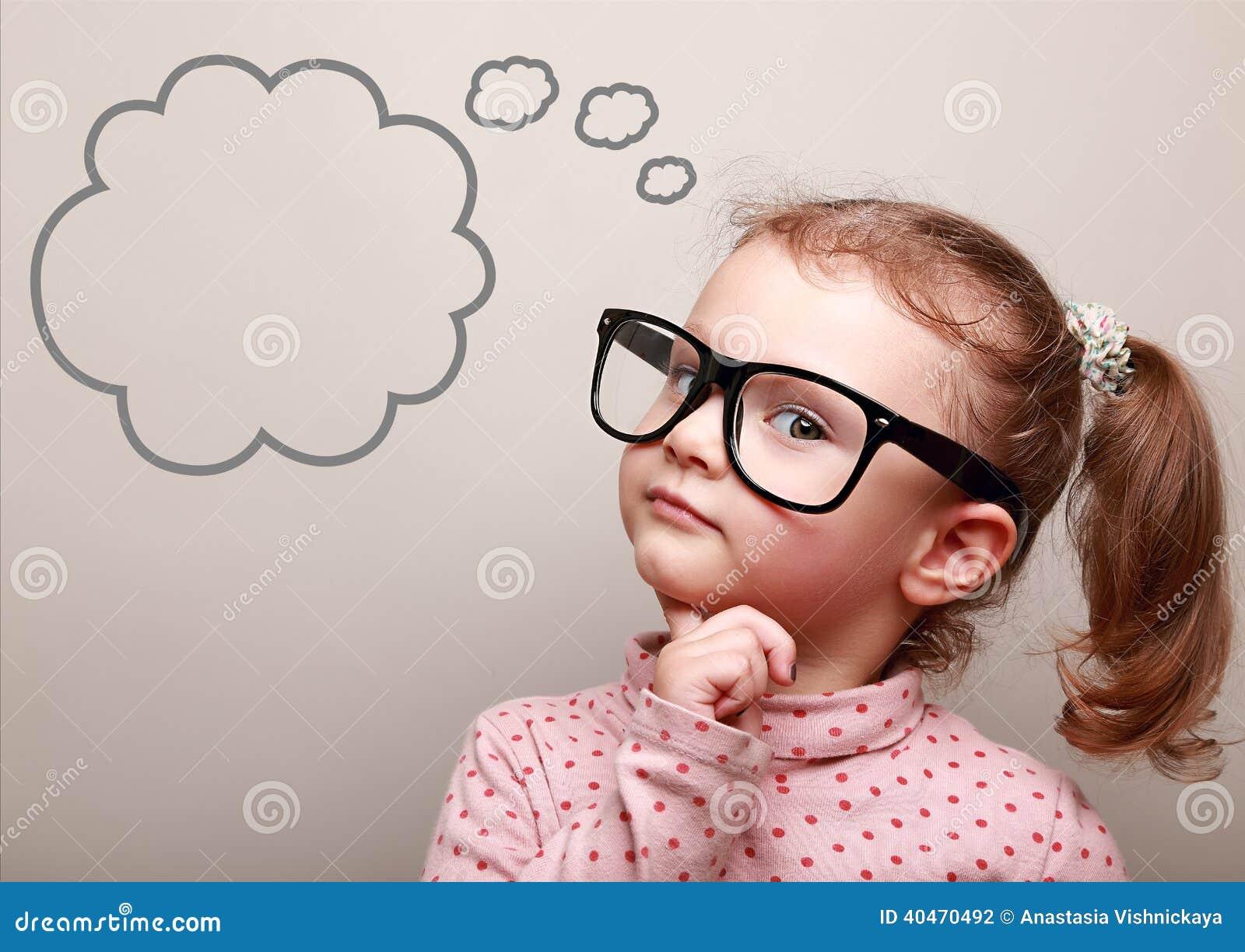 Χαριτωμένο σκεπτόμενο κορίτσι παιδιών στα γυαλιά με την κενή φυσαλίδα