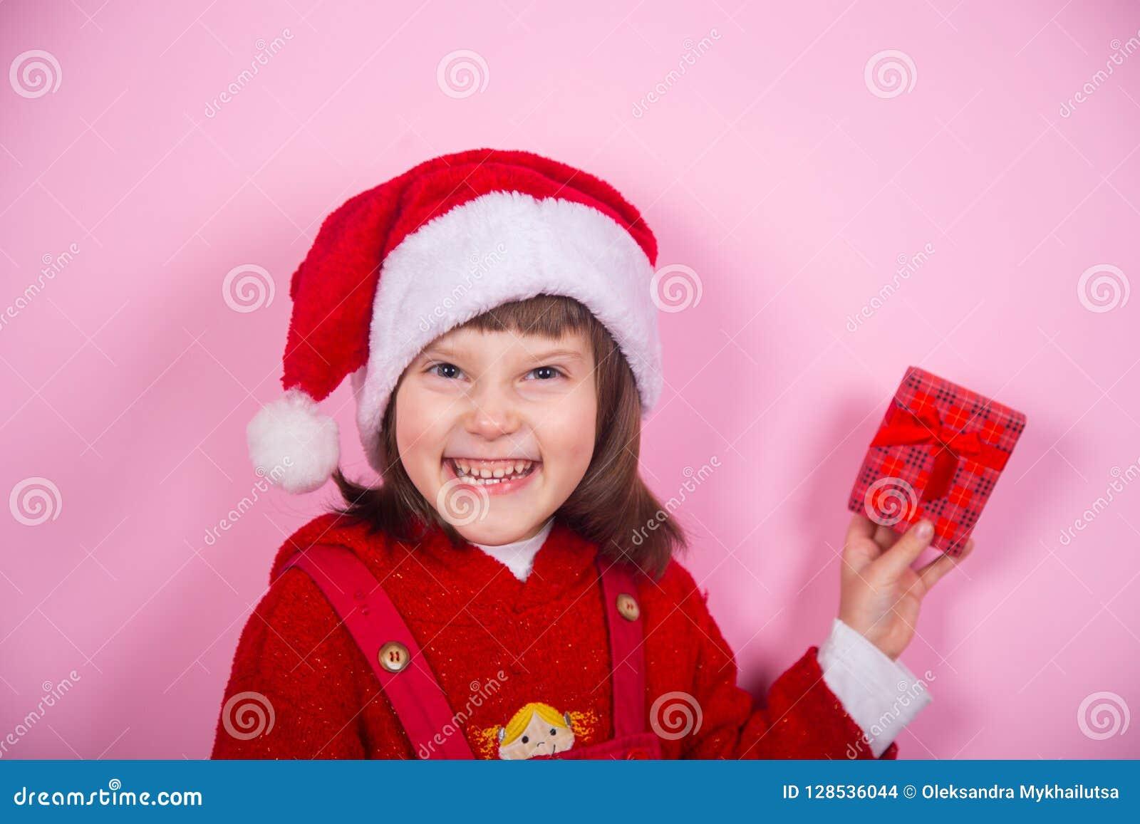Χαριτωμένο χαμογελώντας μικρό κορίτσι στο καπέλο Santa και κοστούμι Χριστουγέννων που κρατά το κόκκινο κιβώτιο δώρων στο στούντιο