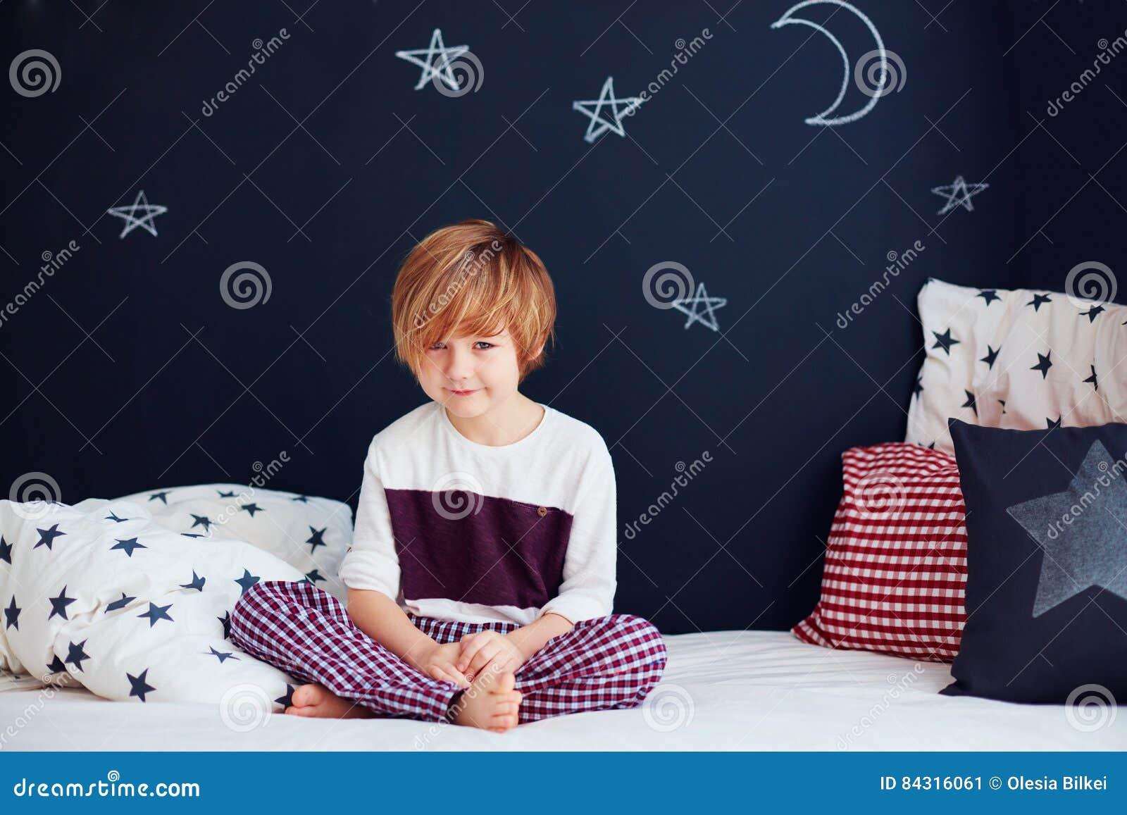 5e69a0714c7f Χαριτωμένο χαμογελώντας παιδί στις πυτζάμες που κάθεται στο κρεβάτι στο  δωμάτιο βρεφικών σταθμών