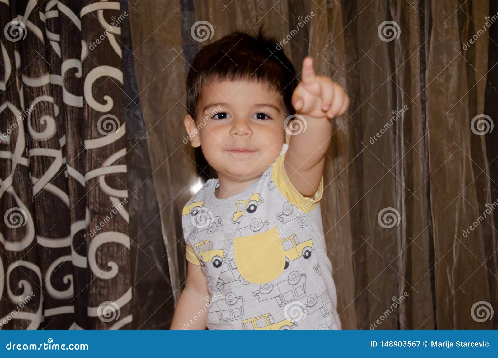 Χαριτωμένο χρονών αγόρι δύο που κάνει τα αστεία πρόσωπα την πρόωρη έννοια ανάπτυξης, πορτρέτο, εκφράσεις προσώπου