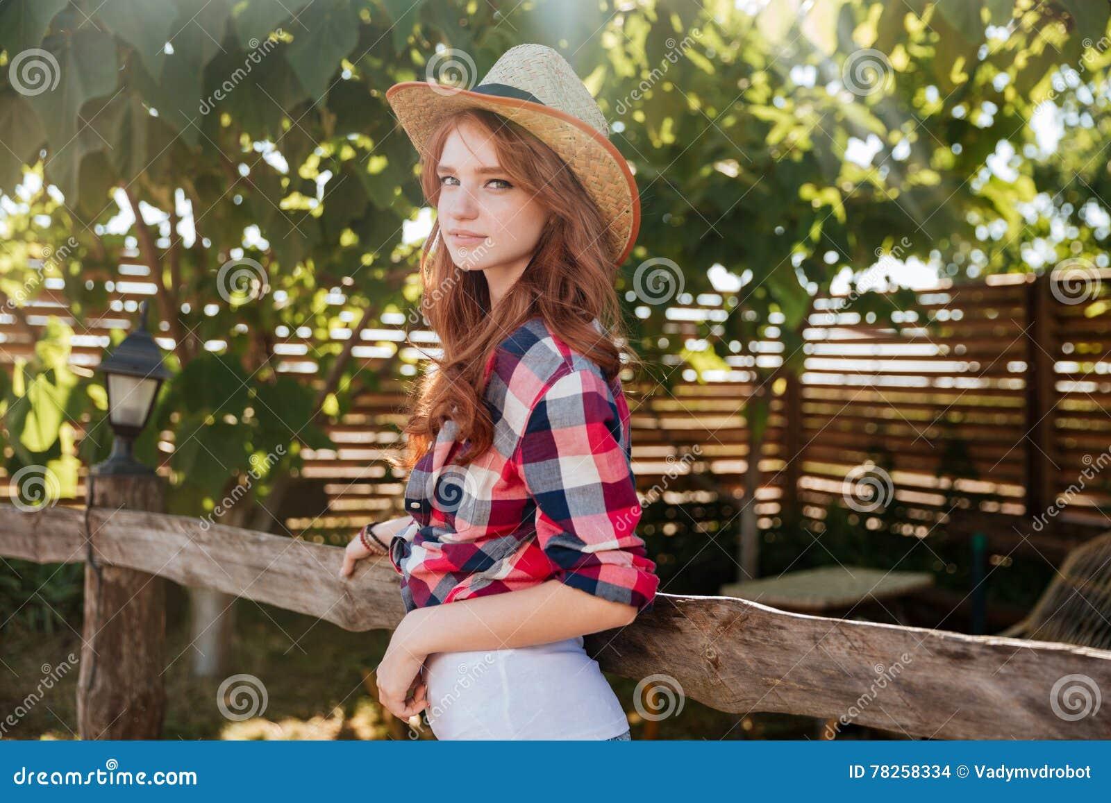 Χαριτωμένο redhead cowgirl χαμόγελου στο καπέλο που κλίνει στο φράκτη αγροκτημάτων