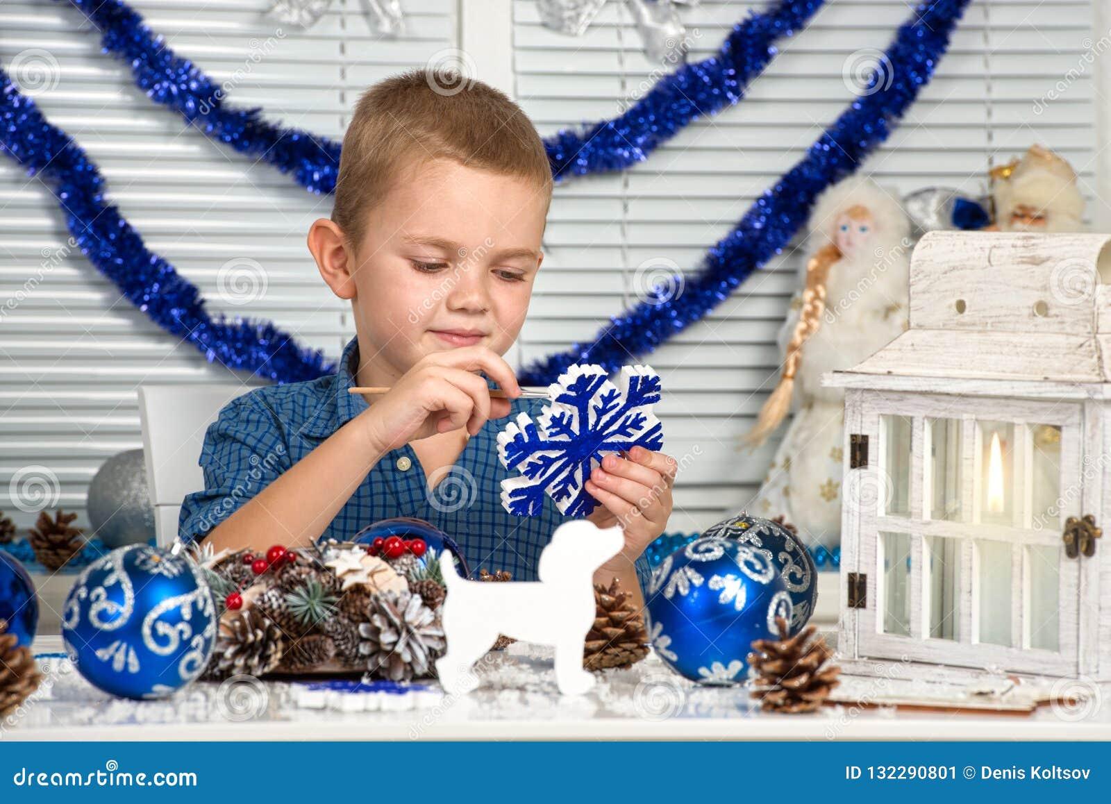 Χαρούμενα Χριστούγεννα και καλές διακοπές! Ένα αγόρι που χρωματίζει snowflake Το παιδί δημιουργεί τις διακοσμήσεις για το εσωτερι