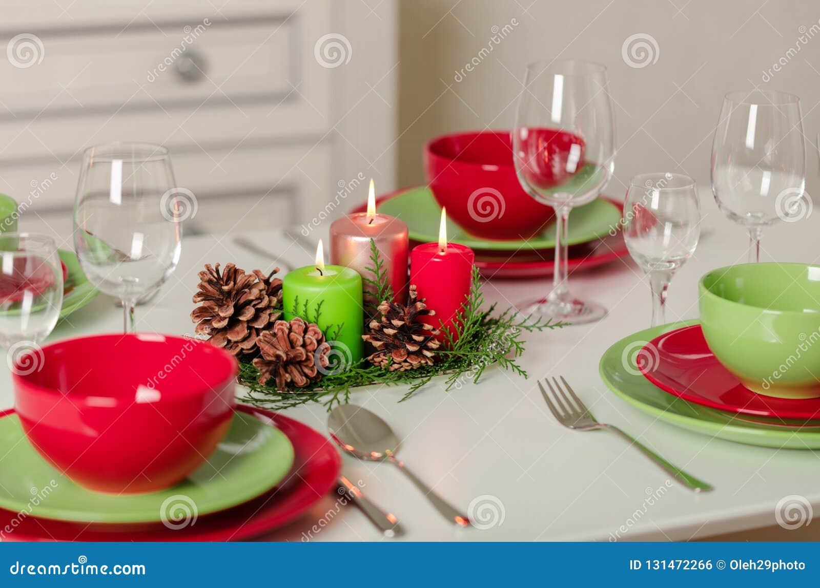 Χαρούμενα Χριστούγεννα και καλή χρονιά! Тable που θέτει το εορταστικό ντεκόρ - πράσινοι και κόκκινοι πιάτα, κεριά και κώνοι έλατ