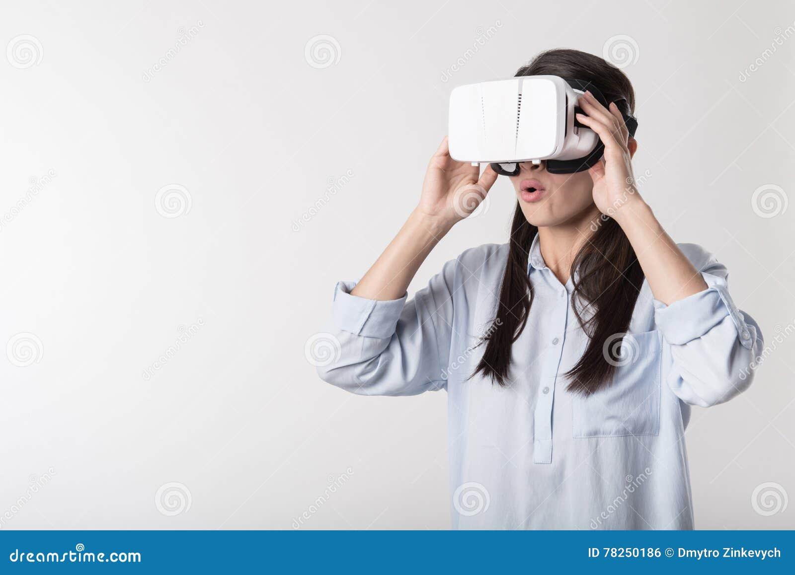 Χαρούμενη γυναίκα που χρησιμοποιεί τη συσκευή εικονικής πραγματικότητας