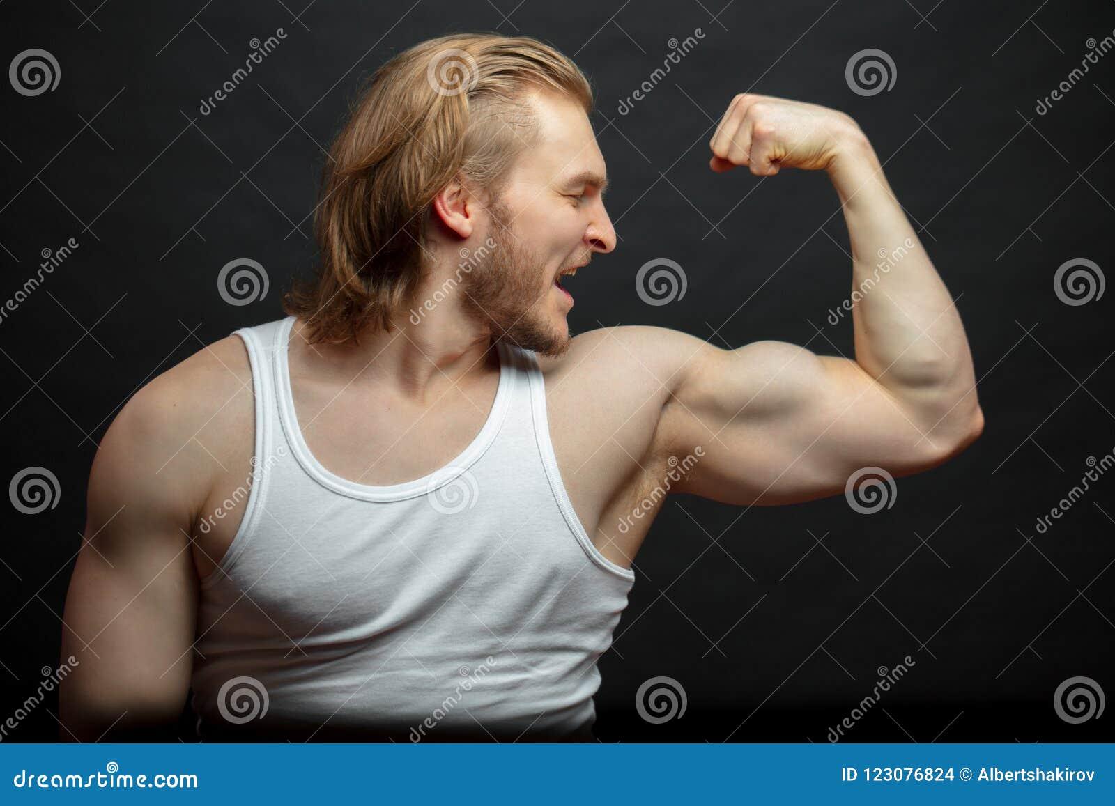 Χαρούμενος θαυμασμός αθλητών με τα ισχυρά όπλα του που απομονώνονται στο μαύρο υπόβαθρο