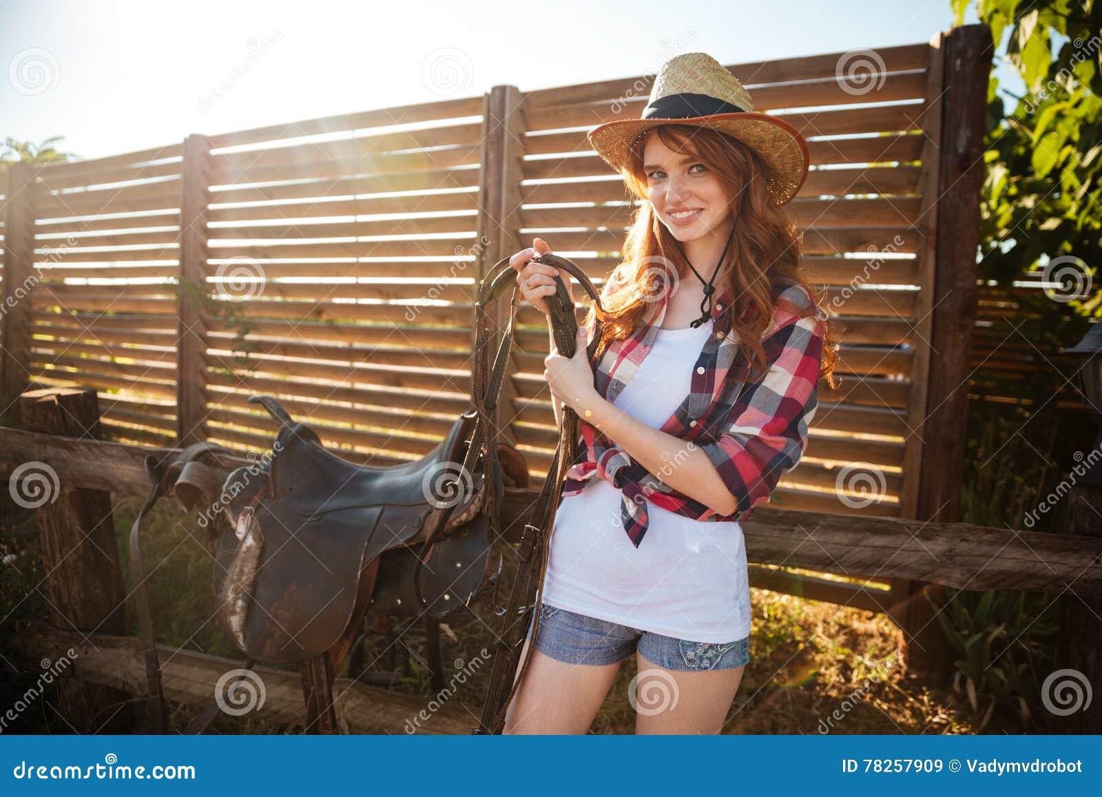 Χαρούμενο redhead νέο cowgirl που προετοιμάζει τη σέλα για την οδήγηση του αλόγου
