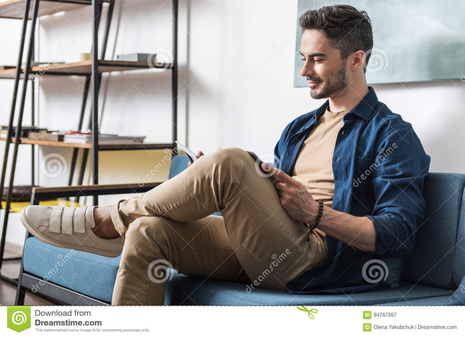 Χαρωπός νεανικός γενειοφόρος τύπος που ξοδεύει τον ελεύθερο χρόνο μέσα στο διαμέρισμα