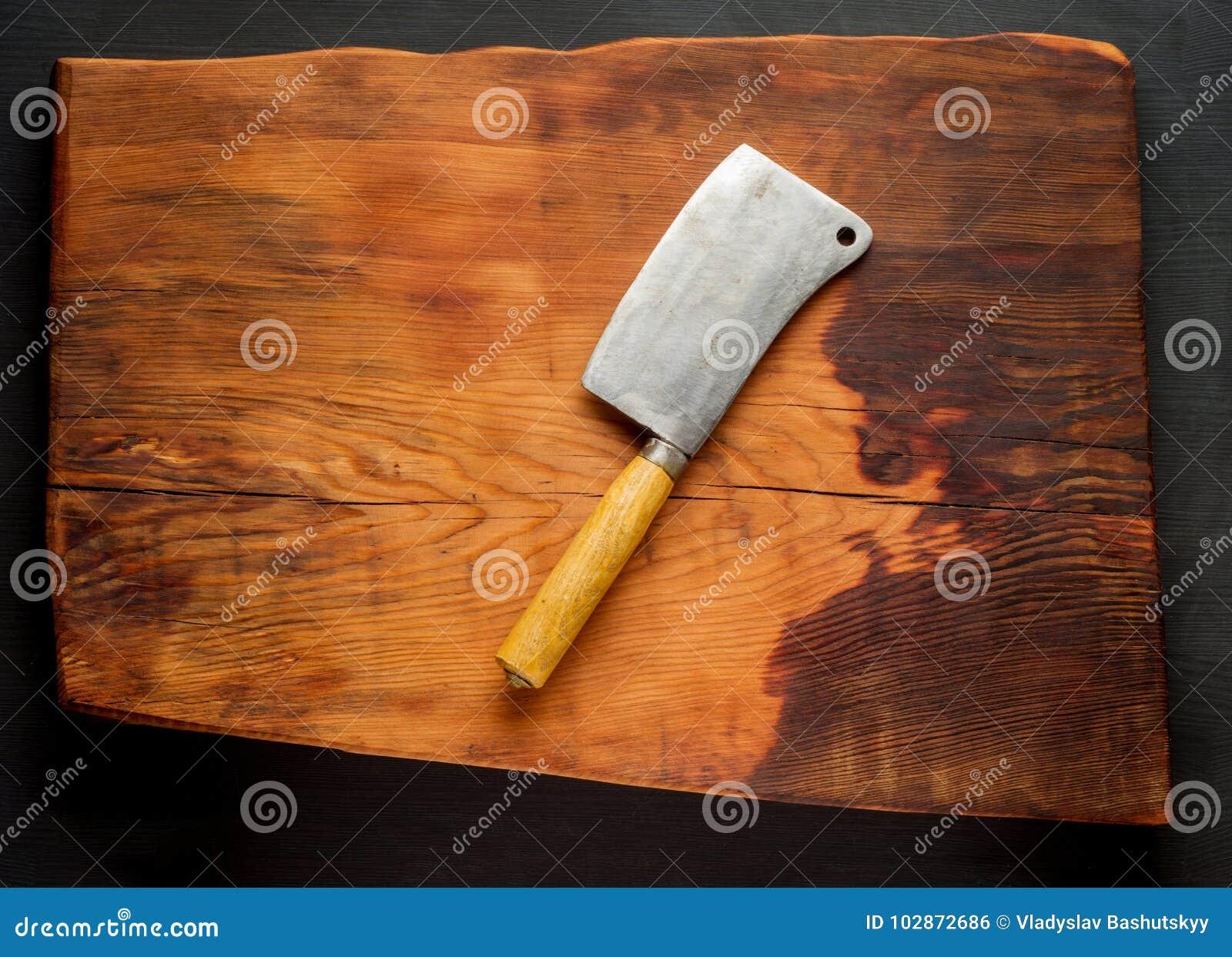 χασάπης Εκλεκτής ποιότητας μπαλτάδες κρέατος χασάπηδων στο σκοτεινό ξύλινο υπόβαθρο πινάκων κουζινών