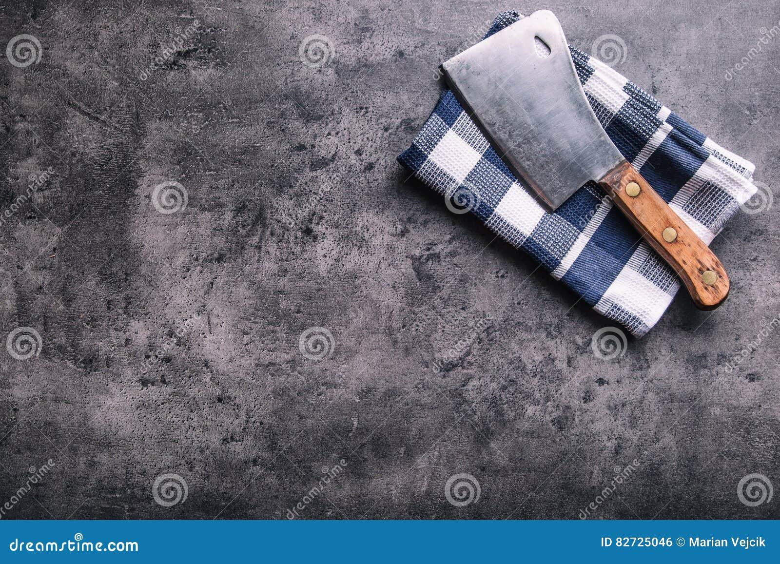 χασάπης Οι εκλεκτής ποιότητας μπαλτάδες κρέατος χασάπηδων με την πετσέτα υφασμάτων στη σκοτεινή συγκεκριμένη ή ξύλινη κουζίνα επι