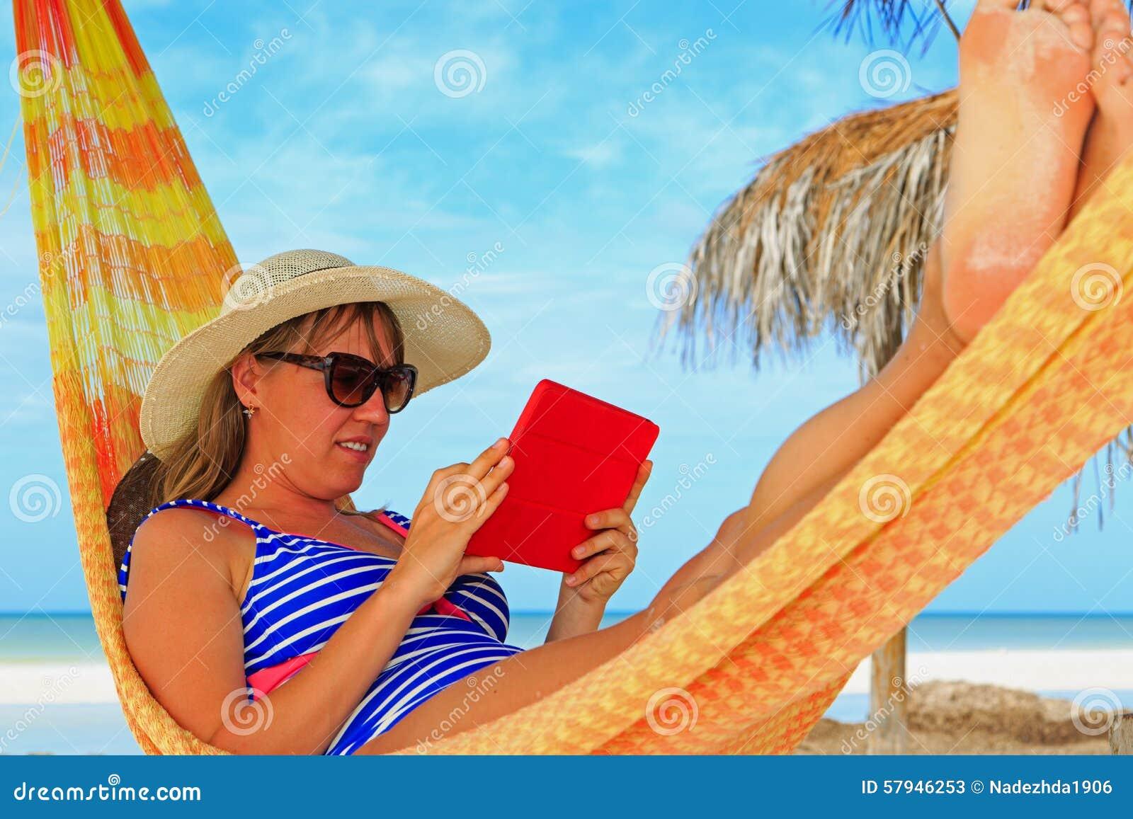 Χαλάρωση γυναικών στο μαξιλάρι αφής hammockwith στη θάλασσα